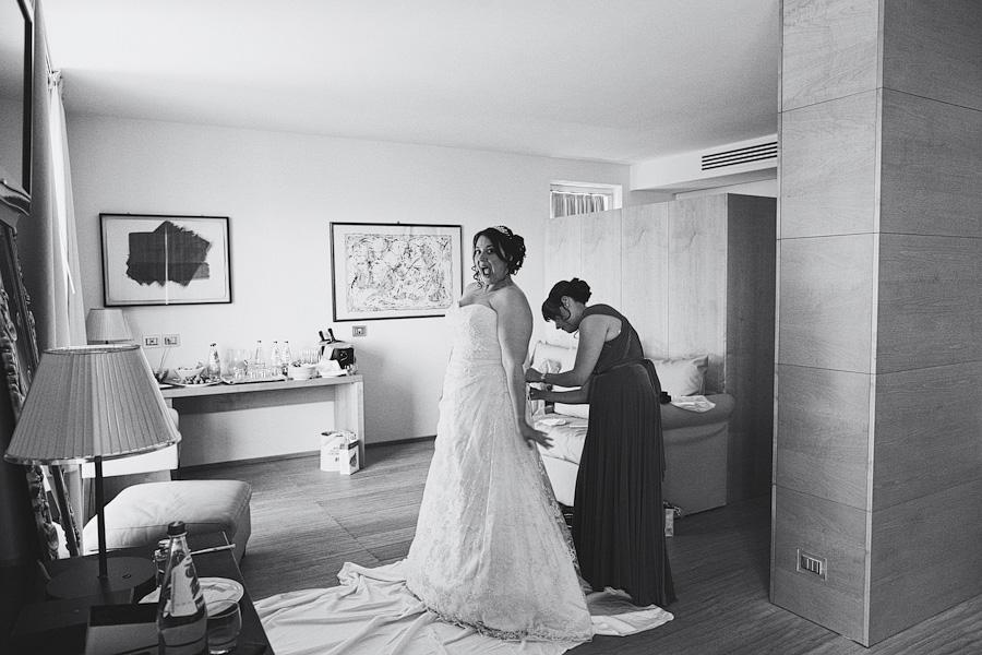 Bride getting in wedding dress