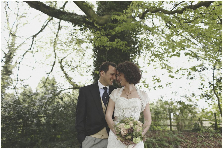 bride and groom portrait next to tree