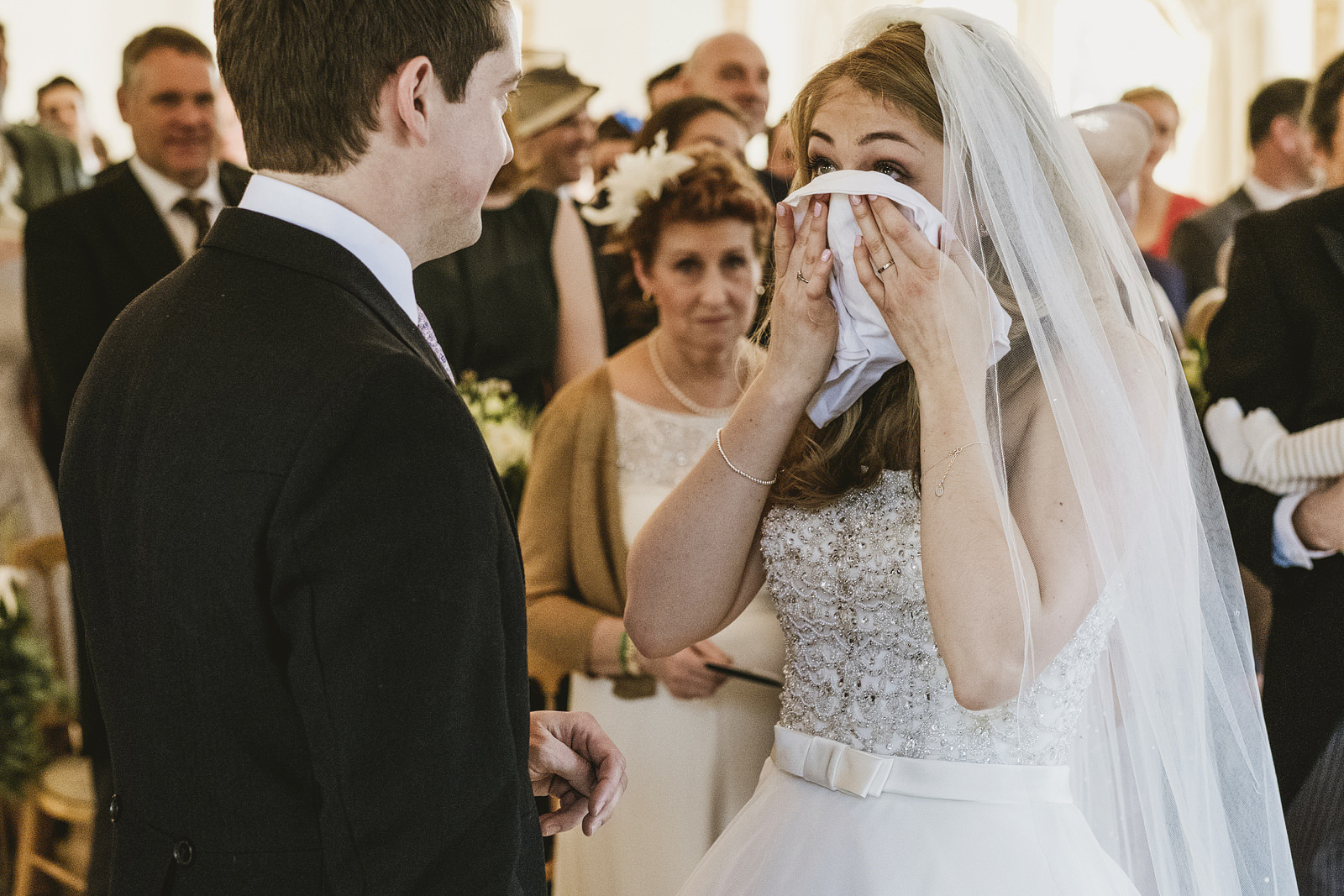 Reportage wedding photographers focus not just on the obvious moments of a ceremony but on the fun, quirky, offbeat moments such as the bride's face half covered by a handkerchief as emotion overcomes her in this example captured at Northbrook Park, UK