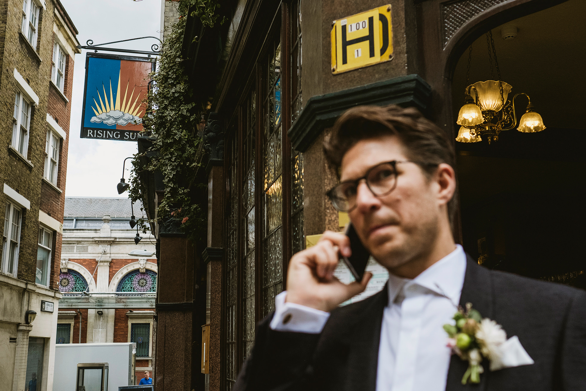 Groom talks on mobile phone on London Street before wedding at the Ned. Photo by York Place Studios