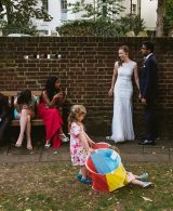 Cecil Sharp House London - a wedding photographer's guide, featured image - wedding guests and bride and groom inside the gardens at Cecil House