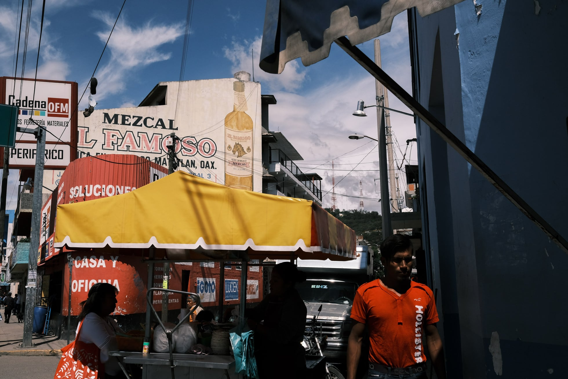 Mexico street photograph - man walks down street with market scene and signposts behind
