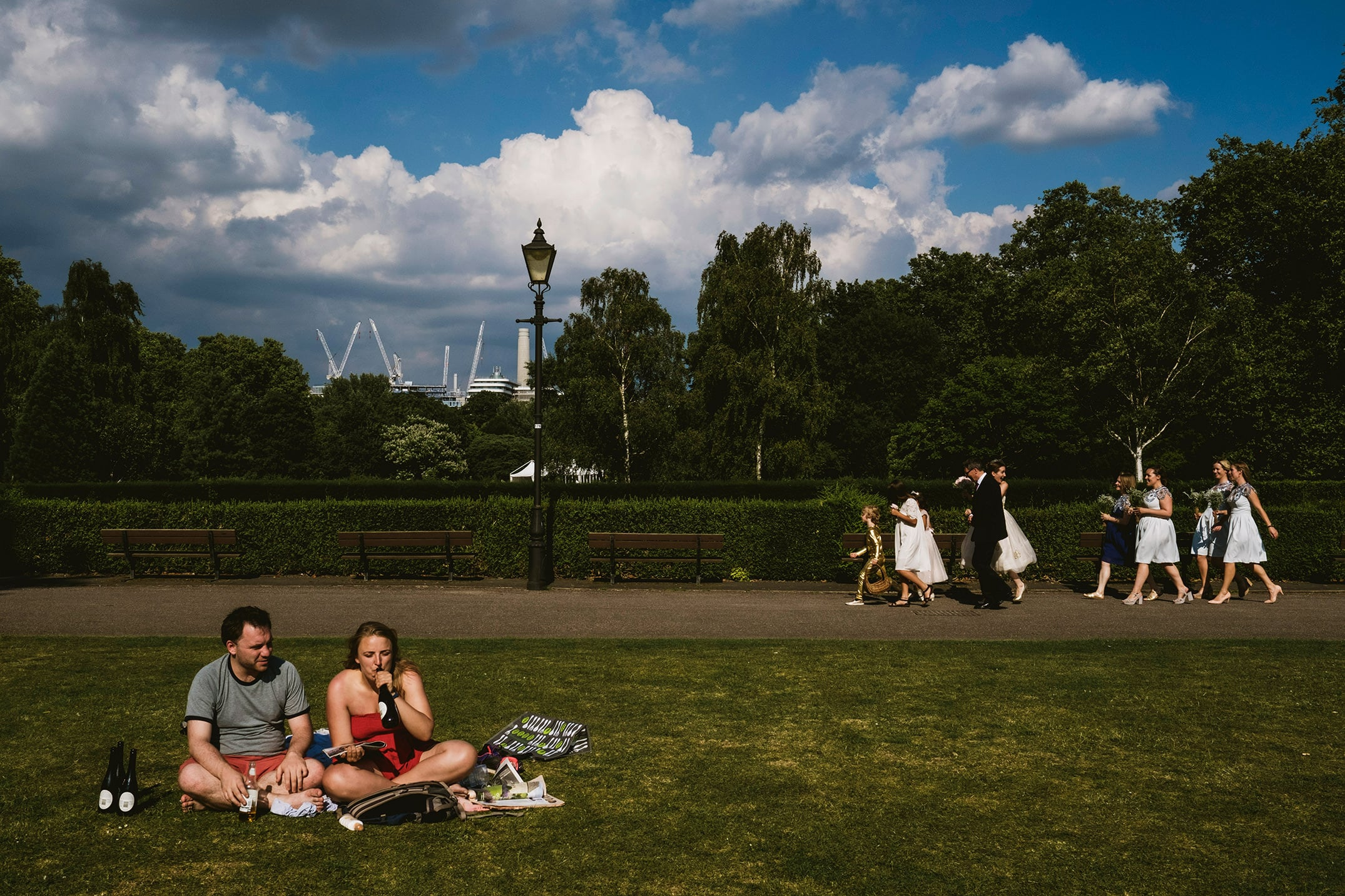 Battersea Park. in London bride walking through the park guests drinking nearby