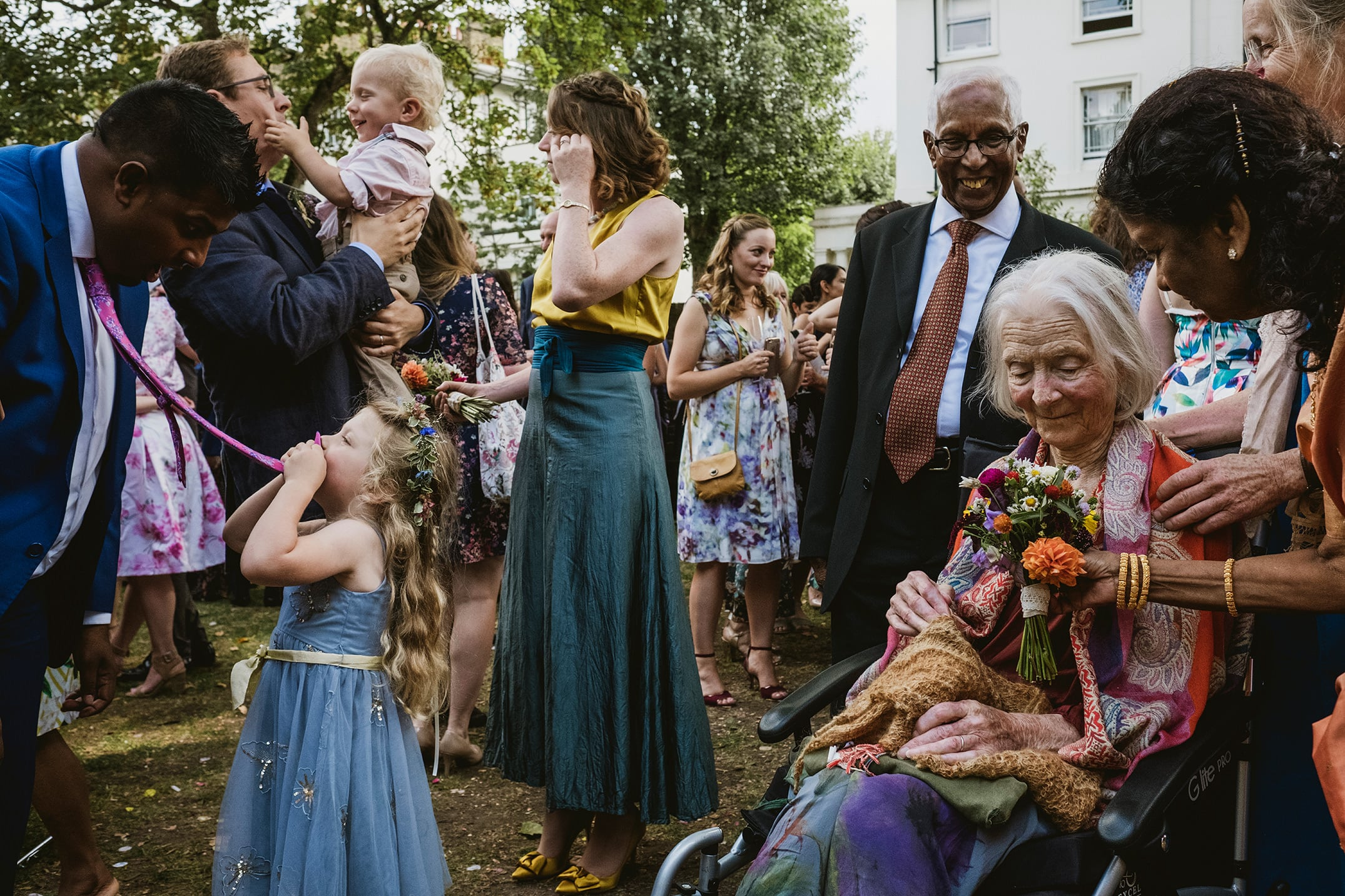 Cecil Sharp House Wedding Photography London Grandma being given flowers and little girl playing with her dad's tie