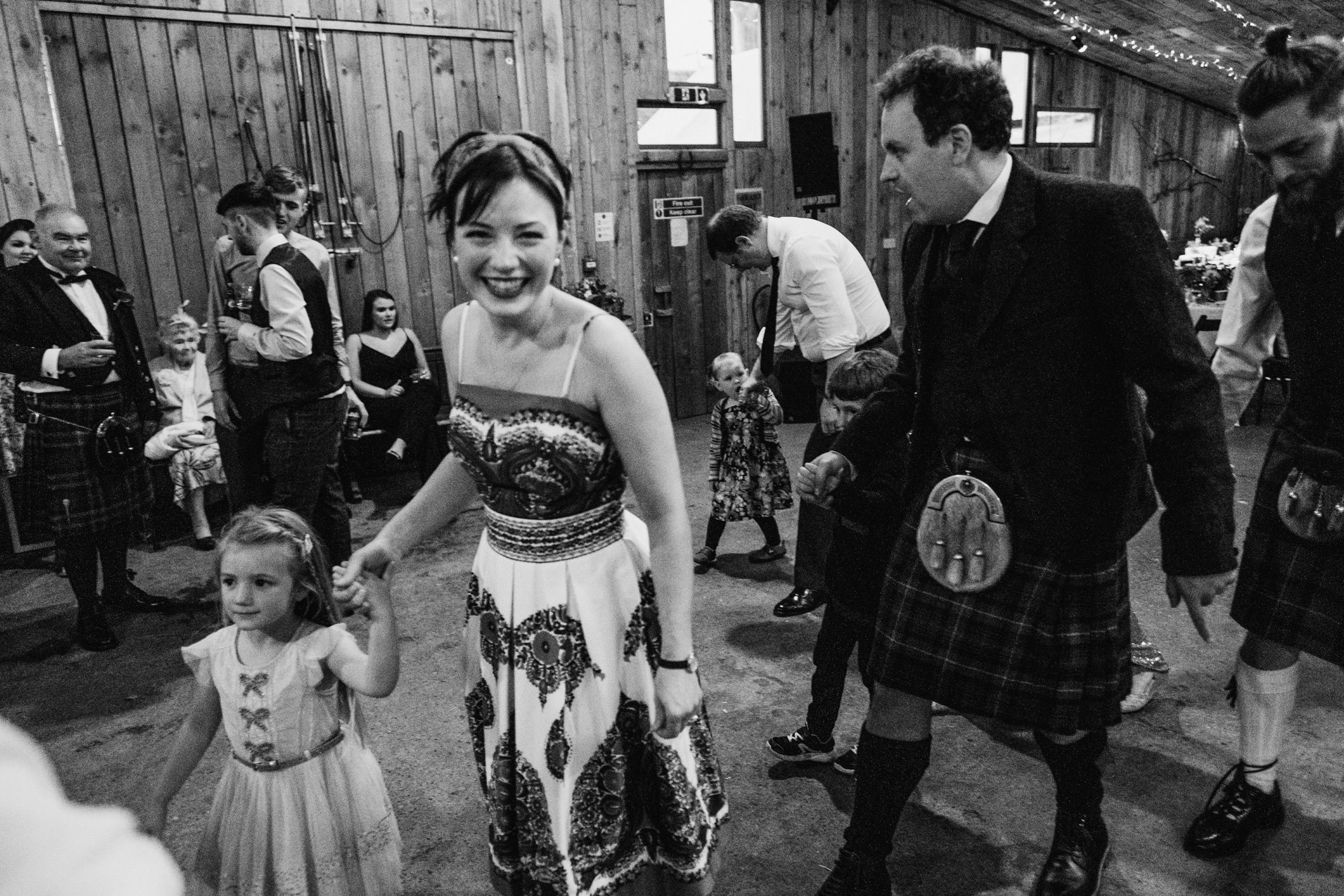 wedding guests ceilidh dancing in a barn