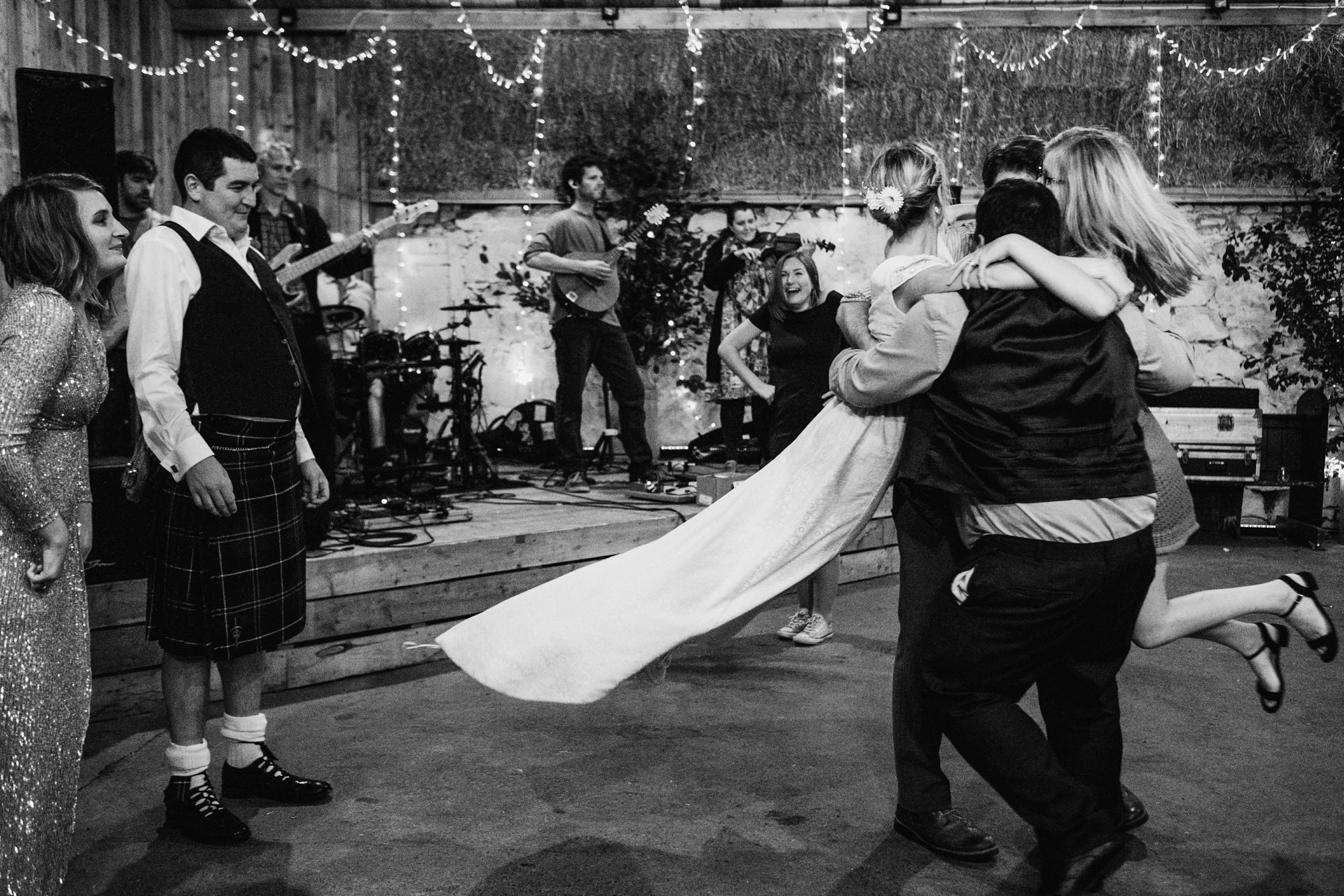 bride, groom and guests ceilidh dancing. Bride in the air