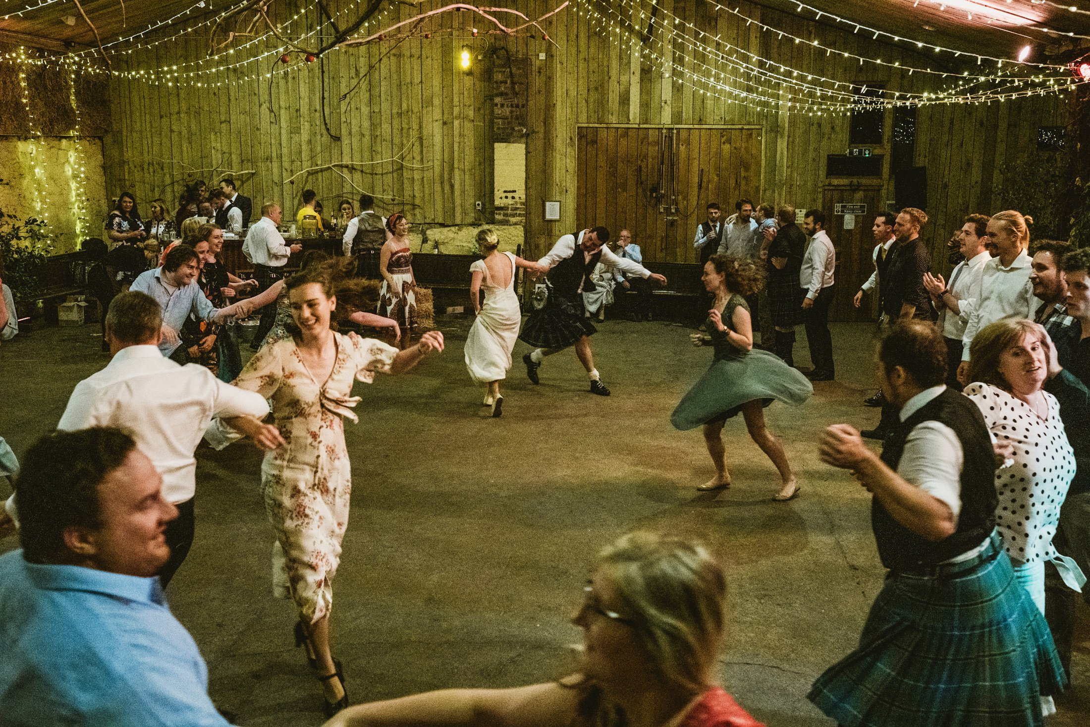 wide shot of the guests ceilidh dancing in the barn