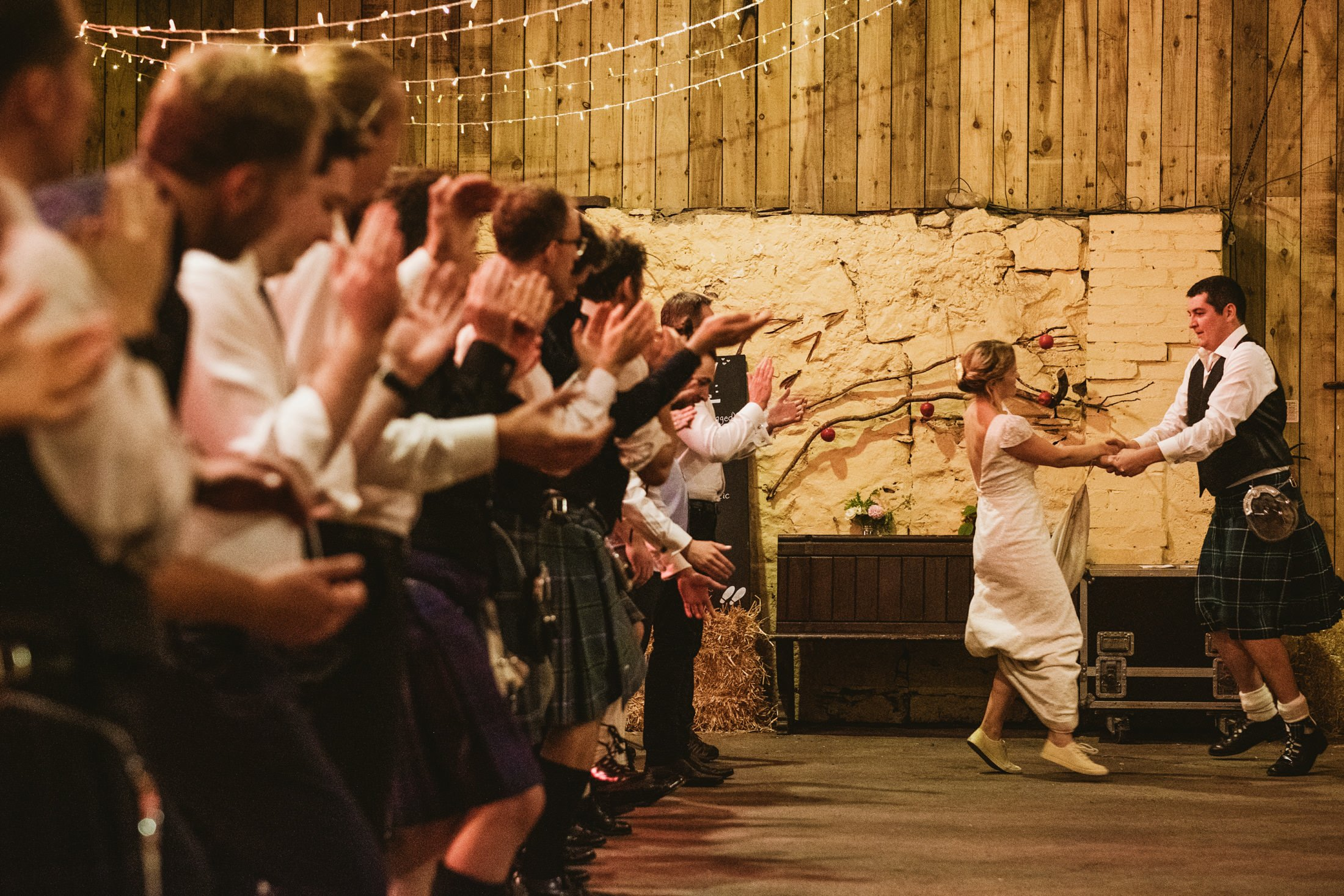 bride and groom ceilidh dancing down the line