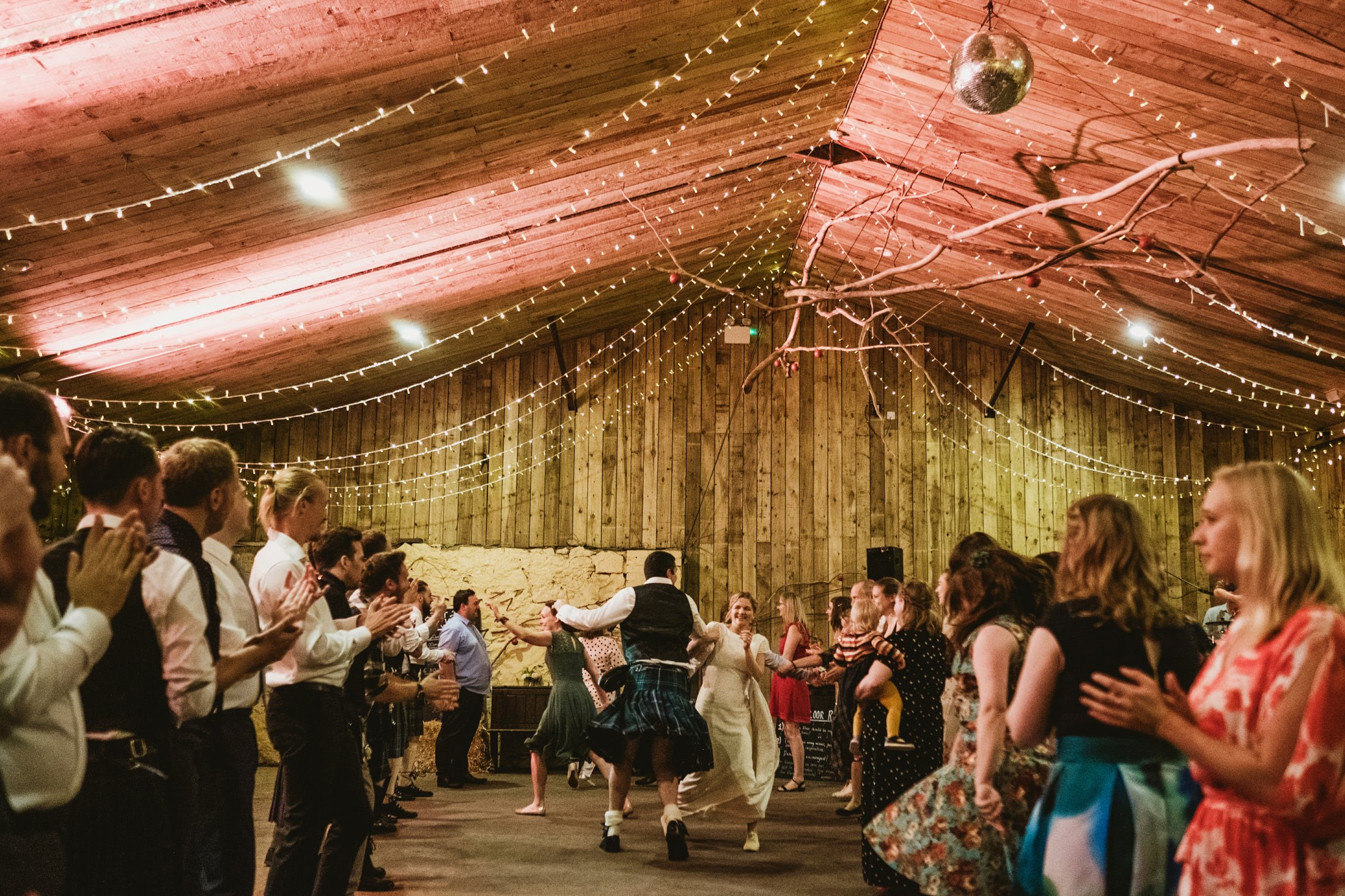 bride and groom ceilidh dancing in the barn at Comrie Croft