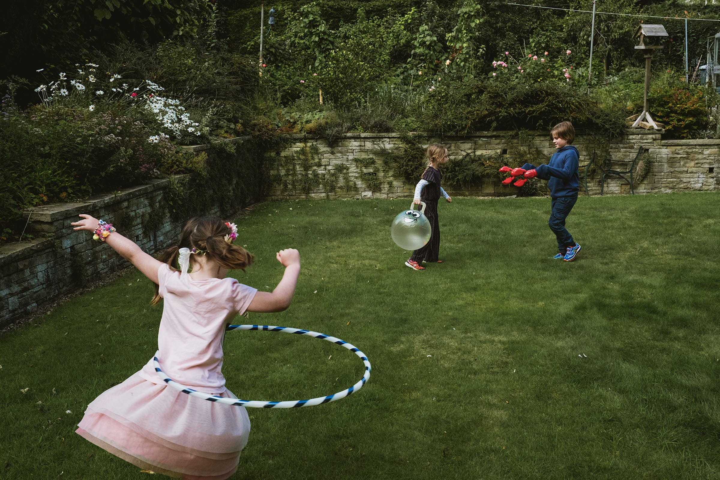 Family Photoshoot at home in the garden by Family Photographers York Place Studios. Front left, girl plays with hula hoop ring, her back to the camera. To her left in the background a girl carries a spacehopper whilst a boy approaches her with toy lobster hands