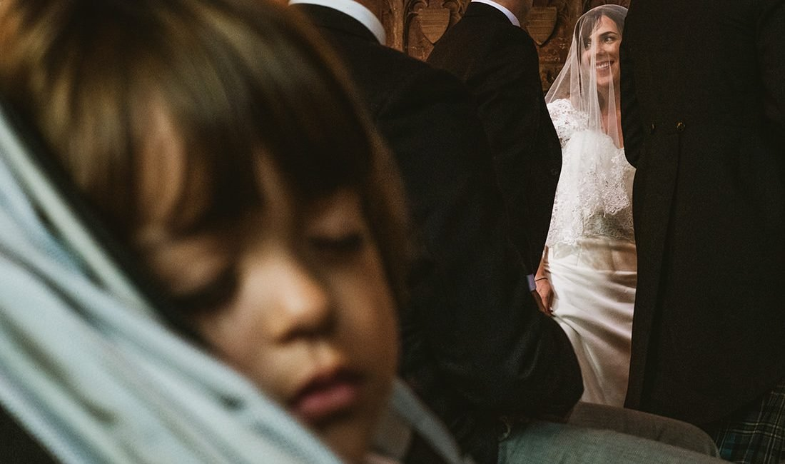 Documentary wedding photograph taken in Cheshire. Little boy sleeping during the ceremony. Bride smiling at her new husband.