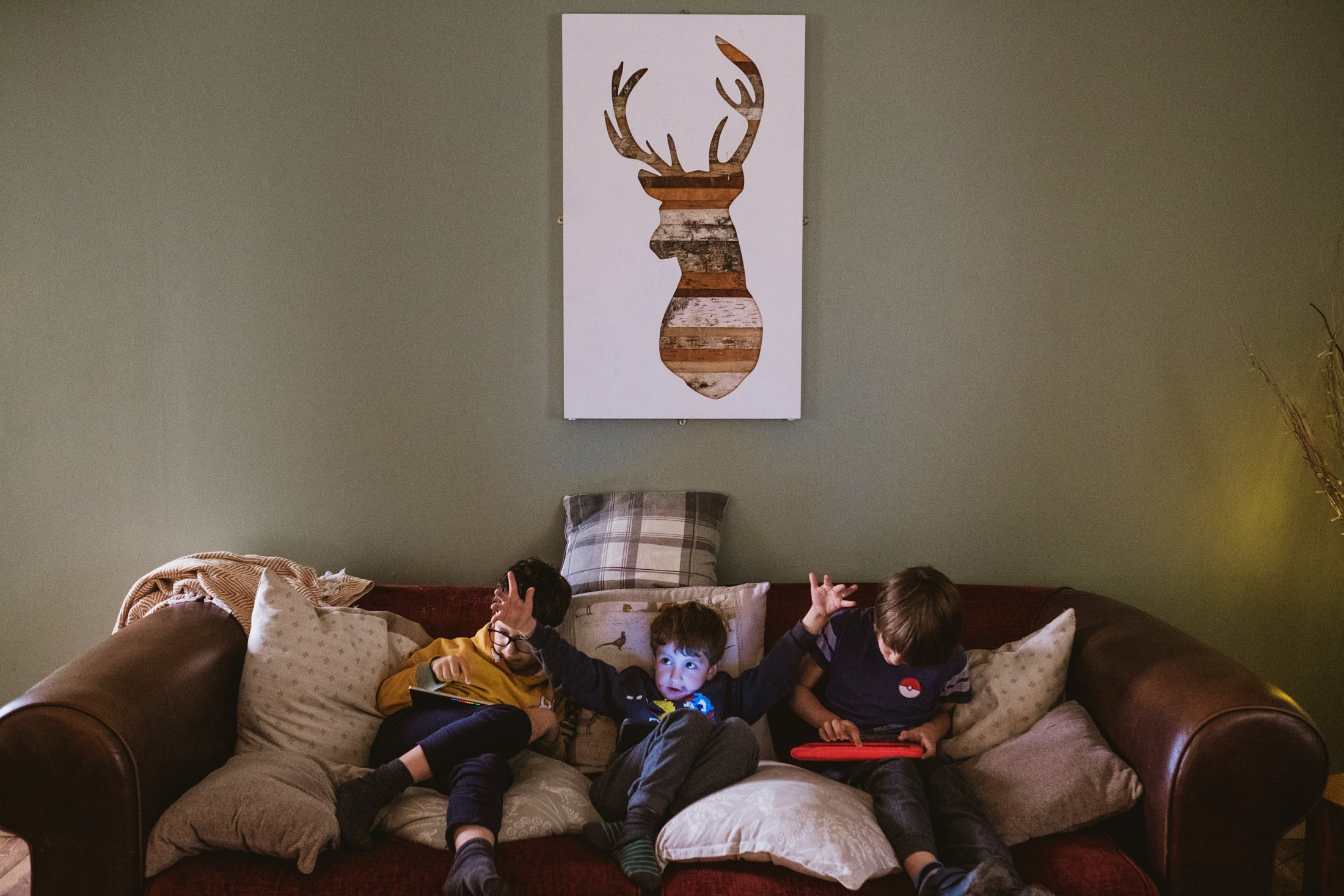 children sat on the sofa playing on electronic devices