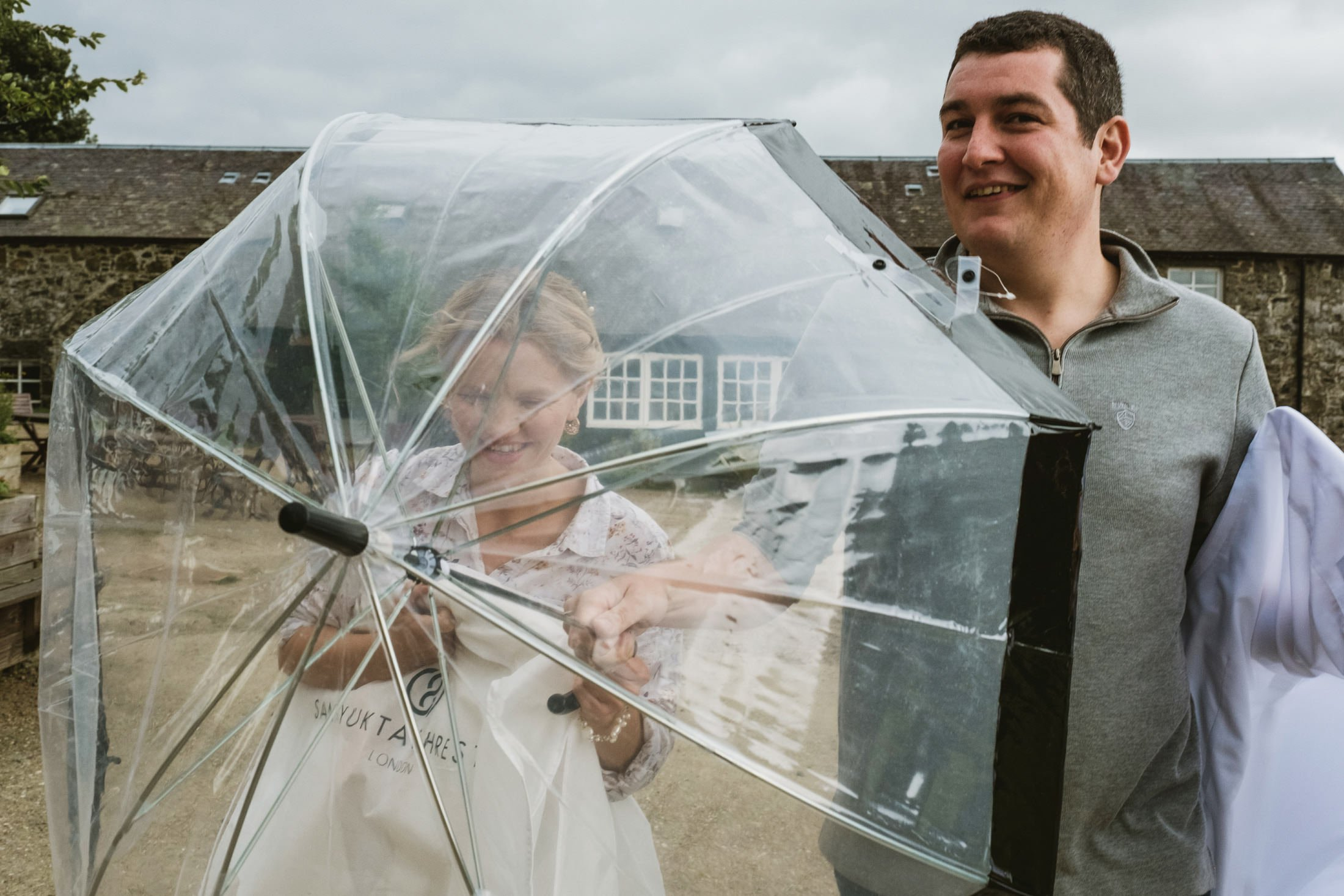 bride and groom walking, bride holding a transparent umbrella