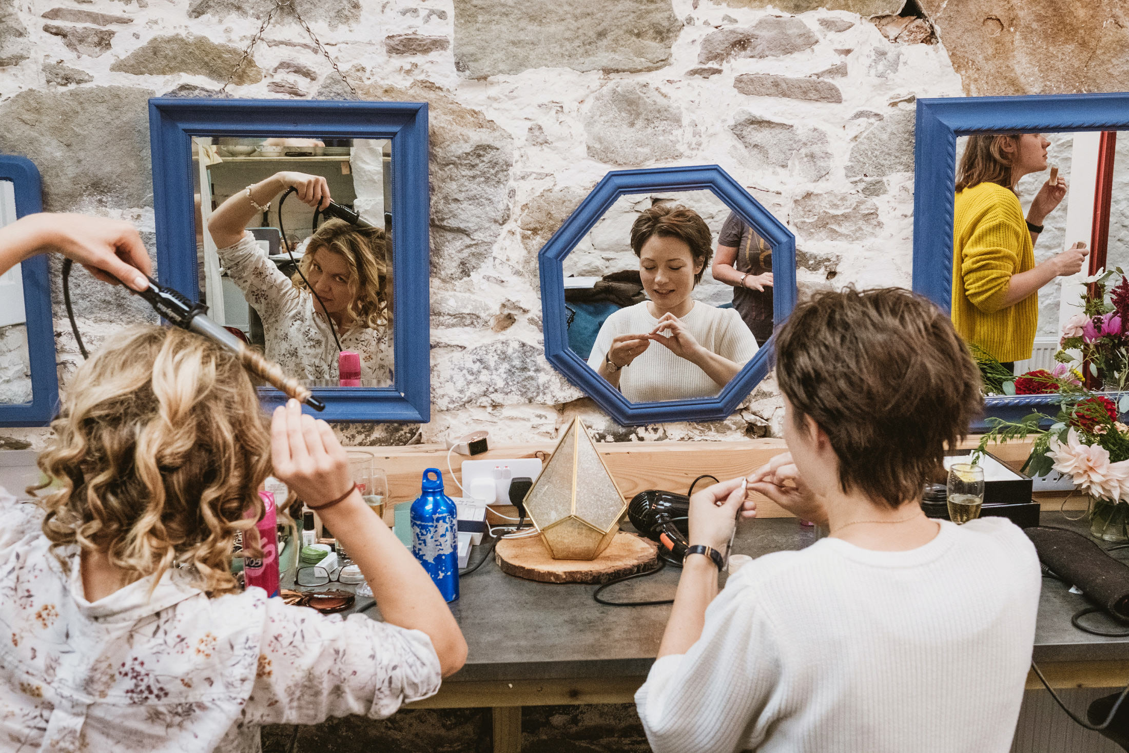 bride and bridesmaids getting ready at Comrie Croft, looking into the mirror