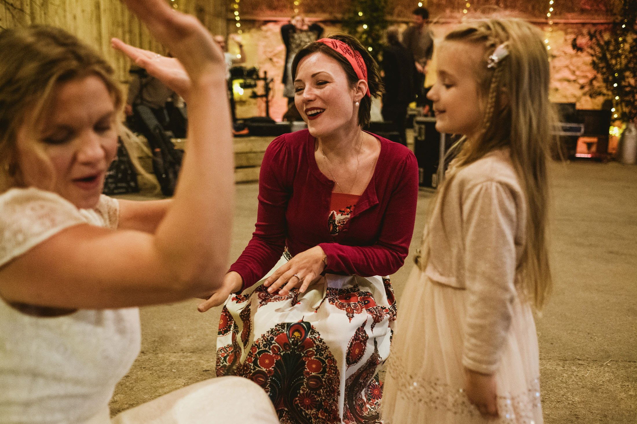 wedding guest with her two children and bride all dancing together