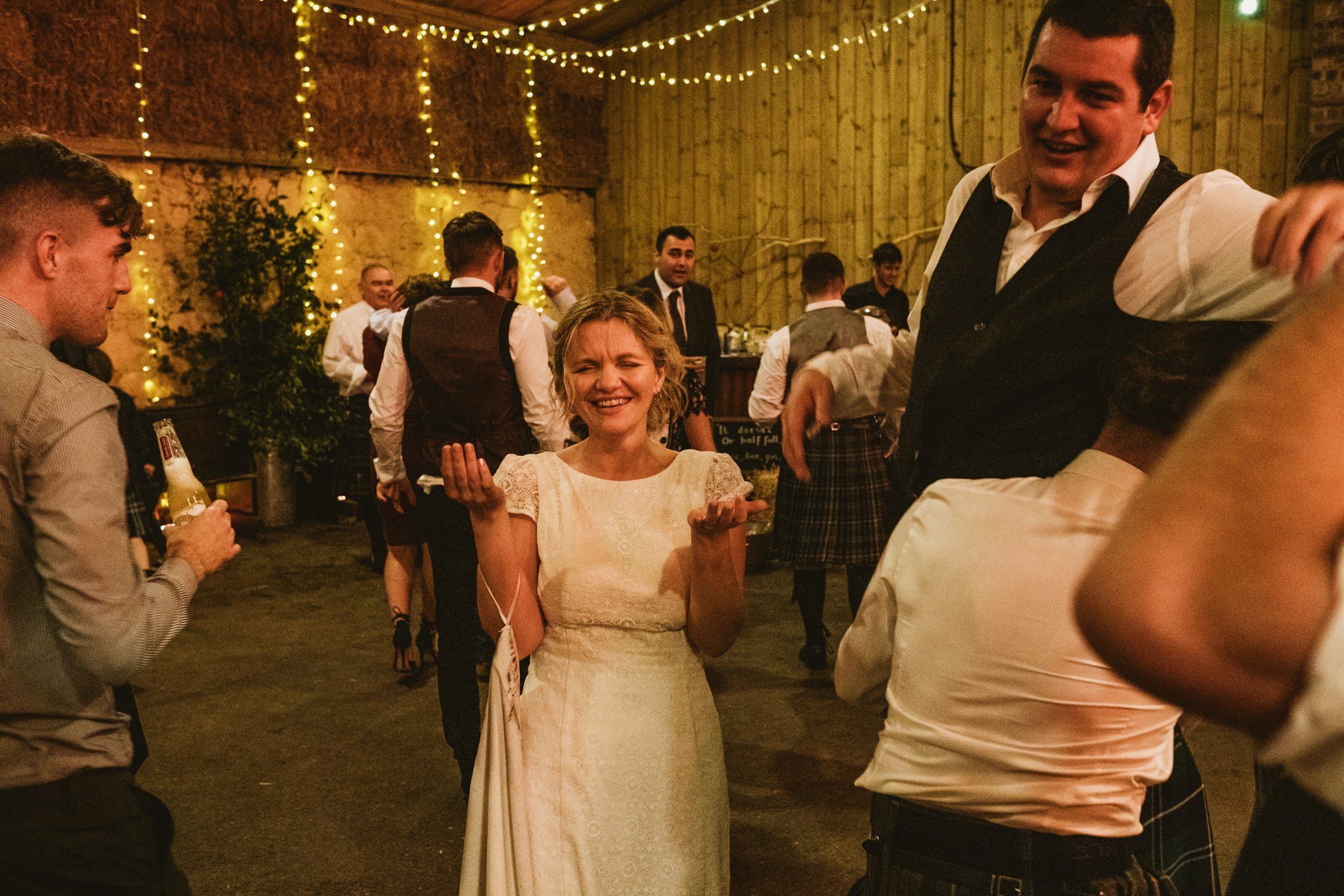 bride laughing and holding hands up whilst groom is lifted into the air by wedding guests