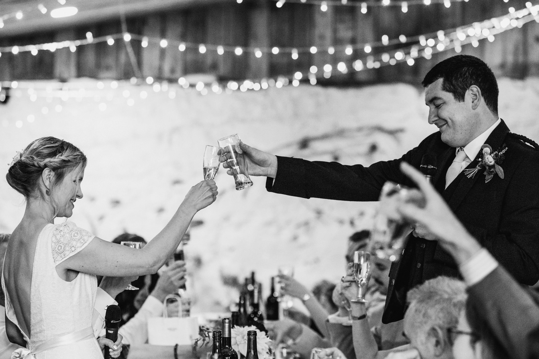 bride and groom clinking glasses during speeches