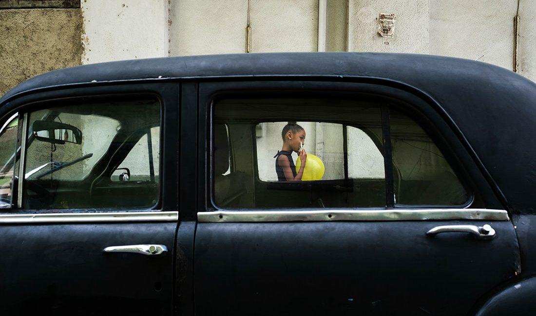 little girl walking past a black Cuban car blowing up a yellow balloon