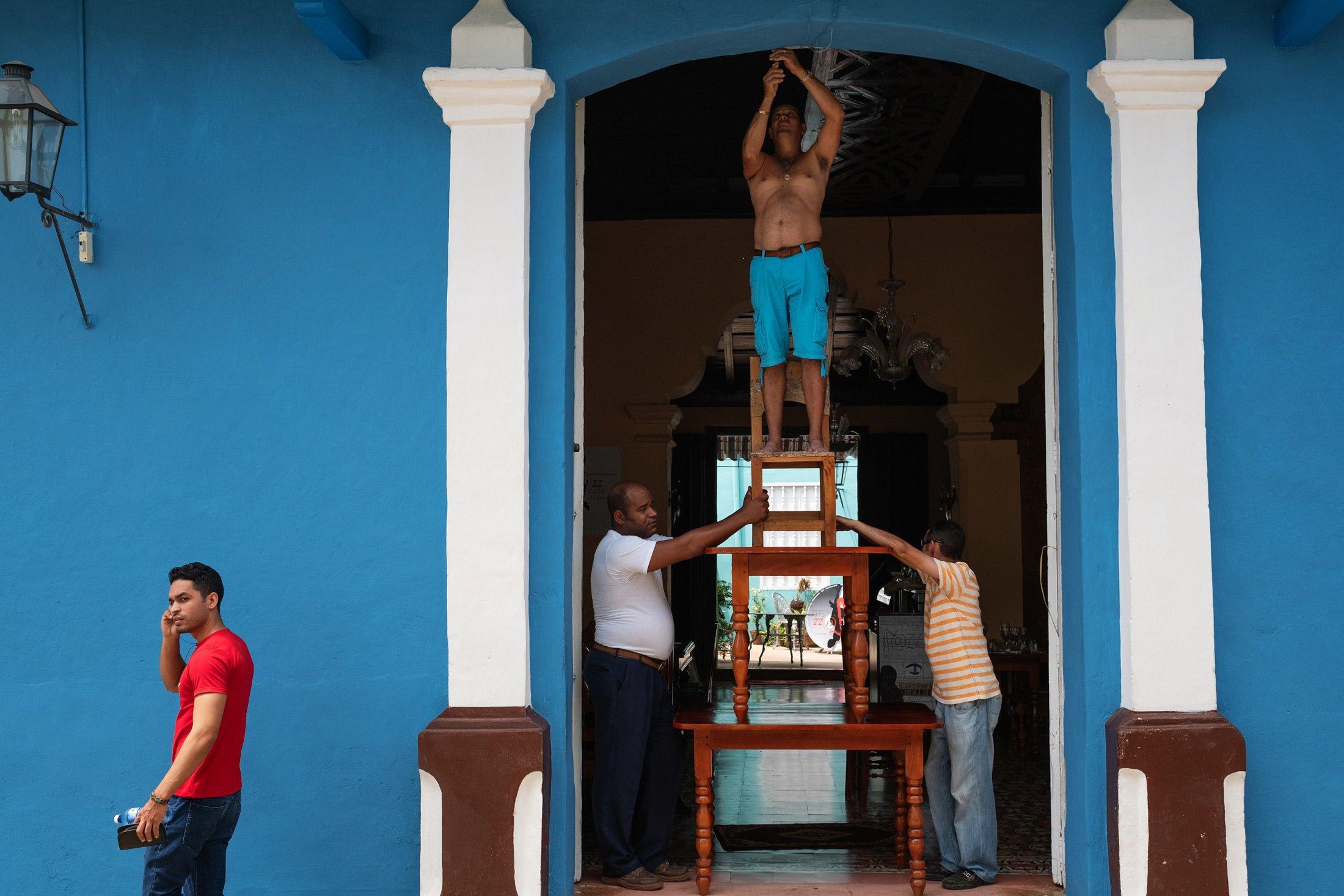 men standing on a chair in Cuba