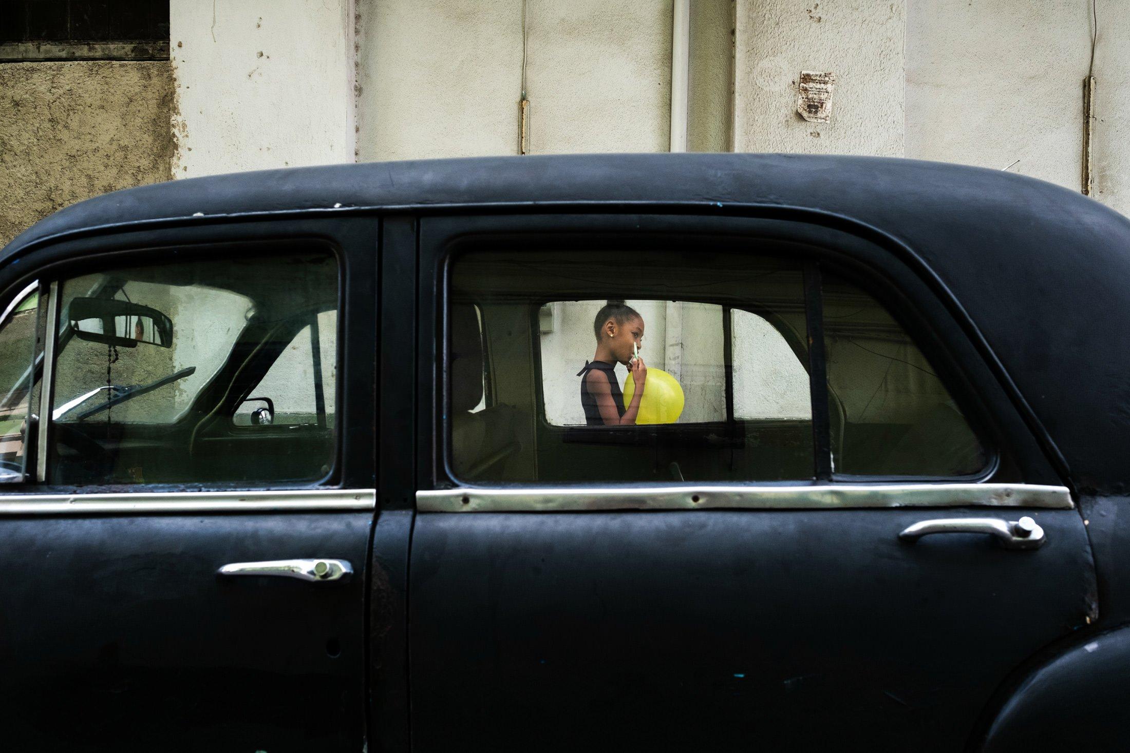 little girl walking past a black Cuban car