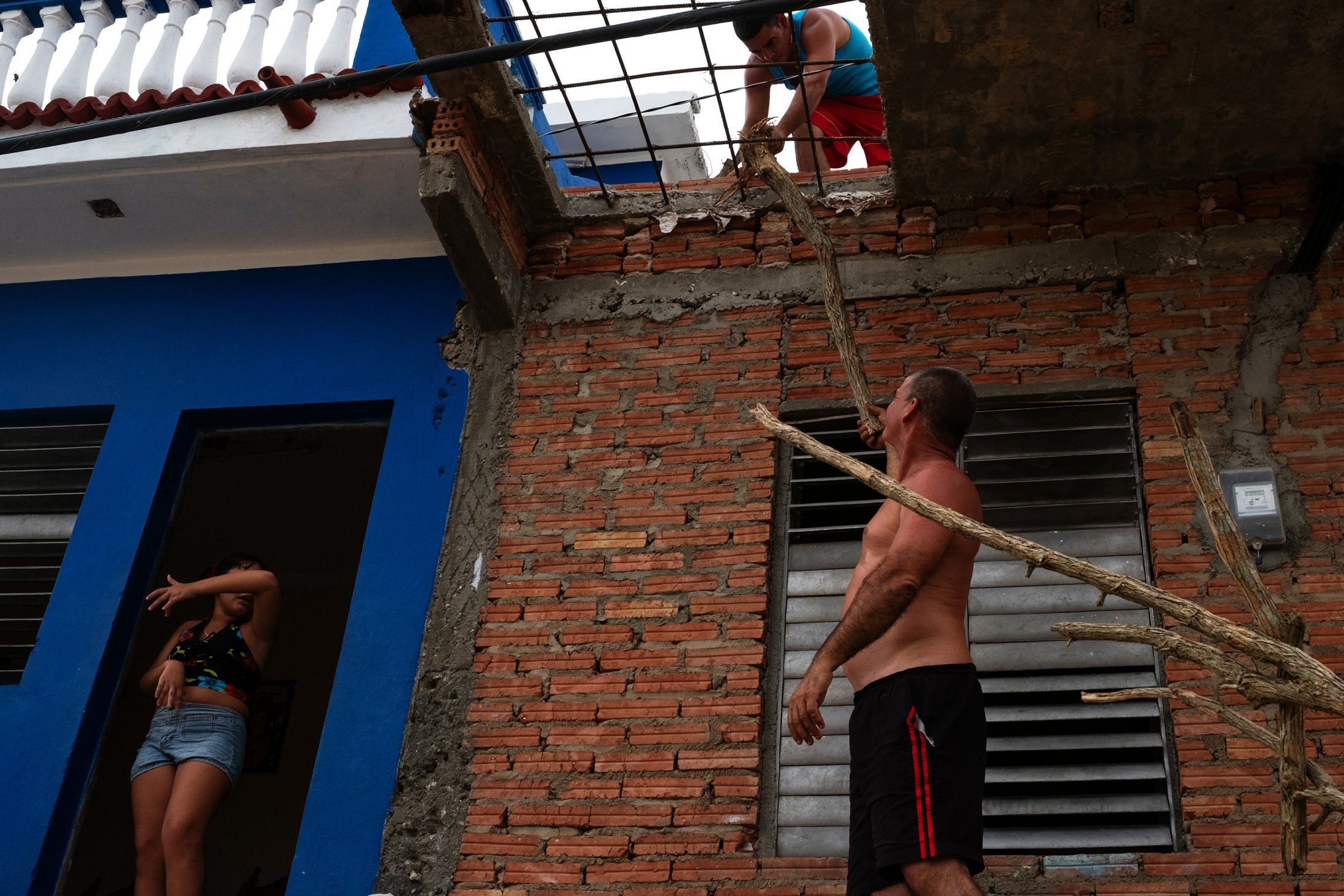 three people working on a house