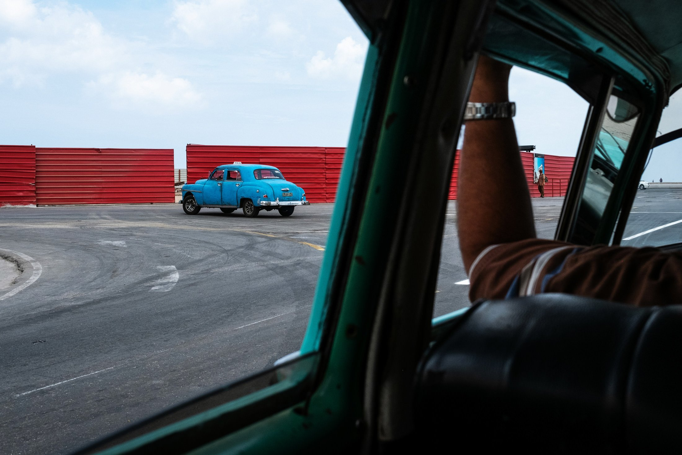 driving down Havana's Malecon looking at a blue car