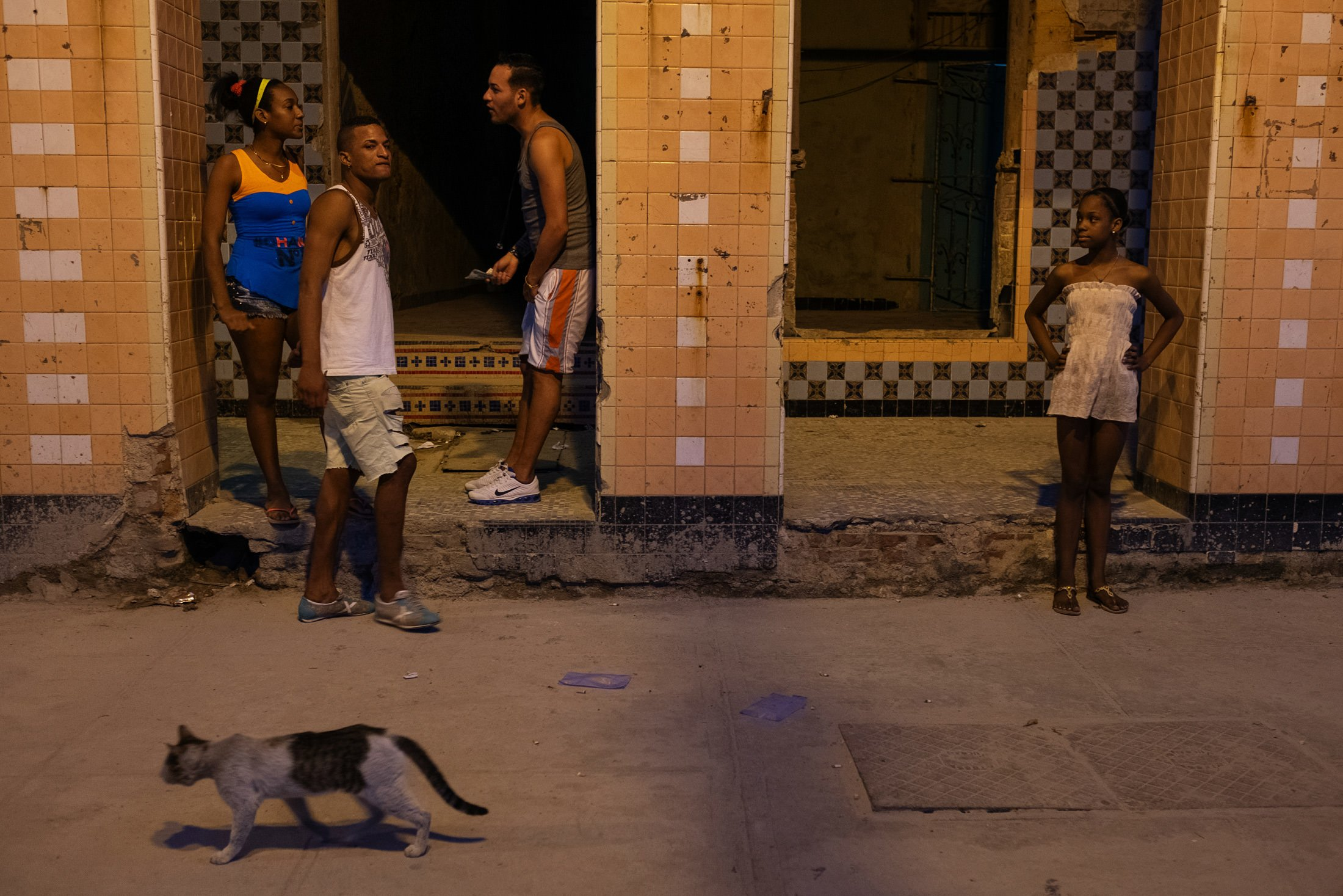 four people and a black and white cat on the Havana's Malecon