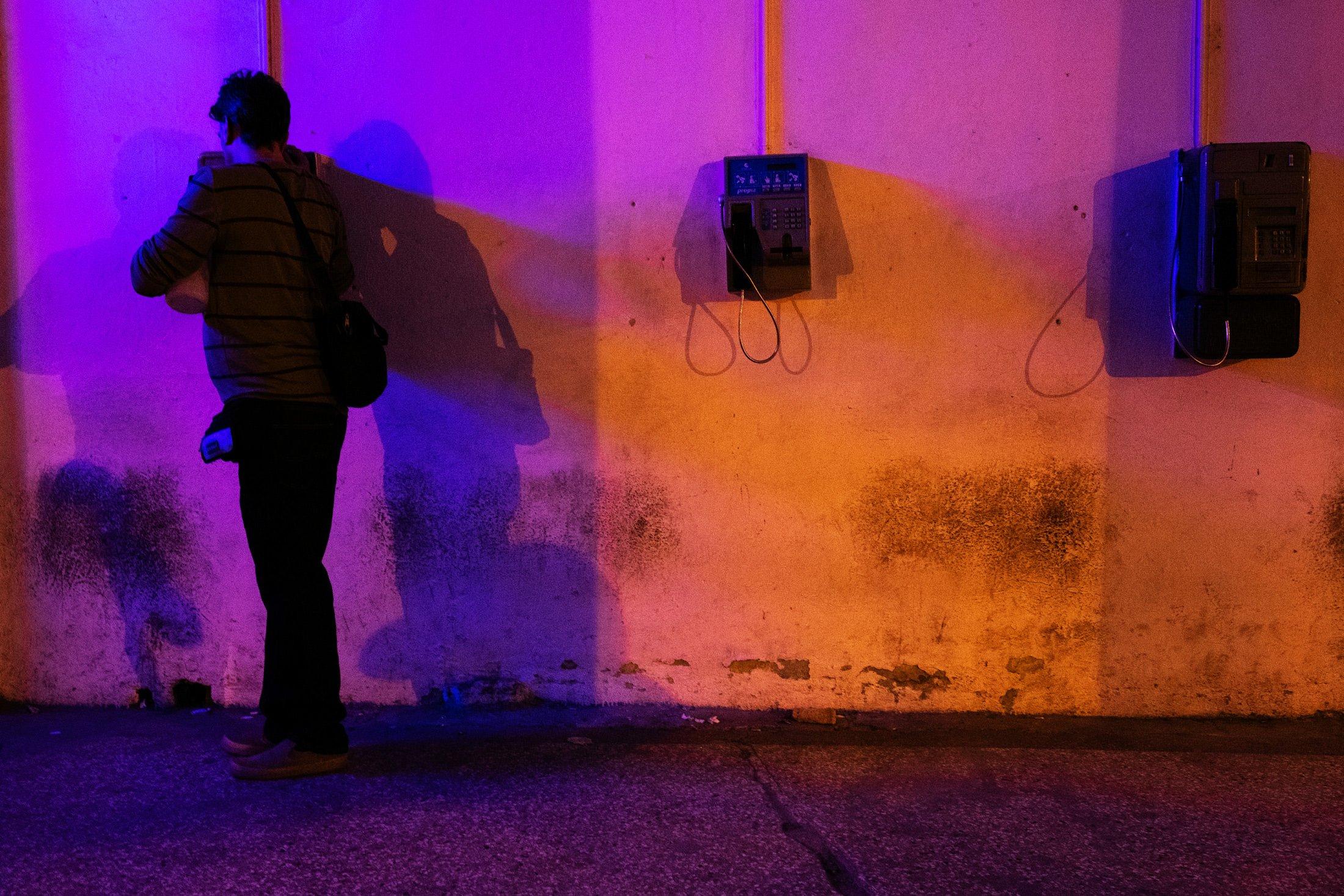 a man on a phone in coloured lights in Havana, Cuba