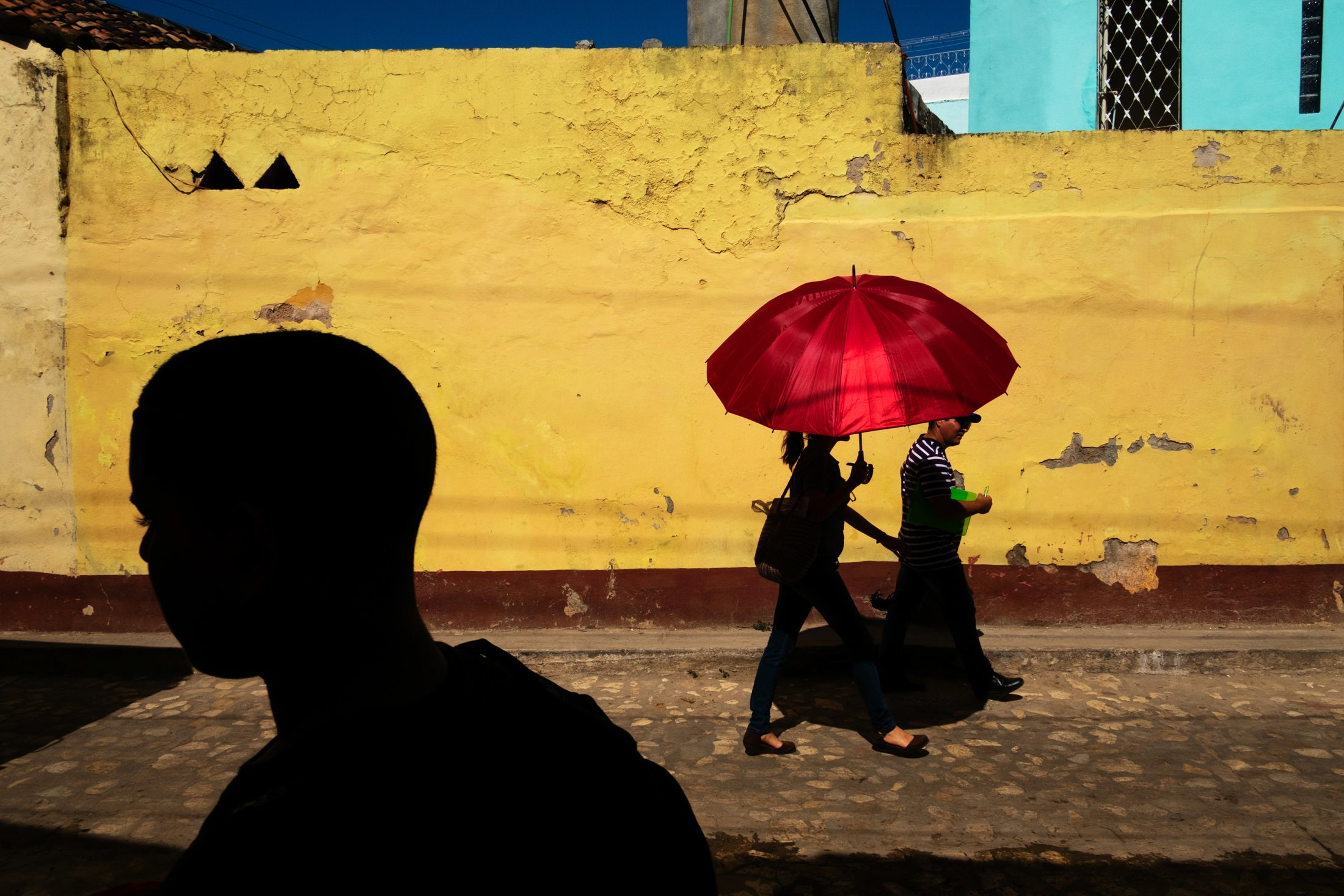 silhouette of a child walking past two people holding a red umbrella in Cuba