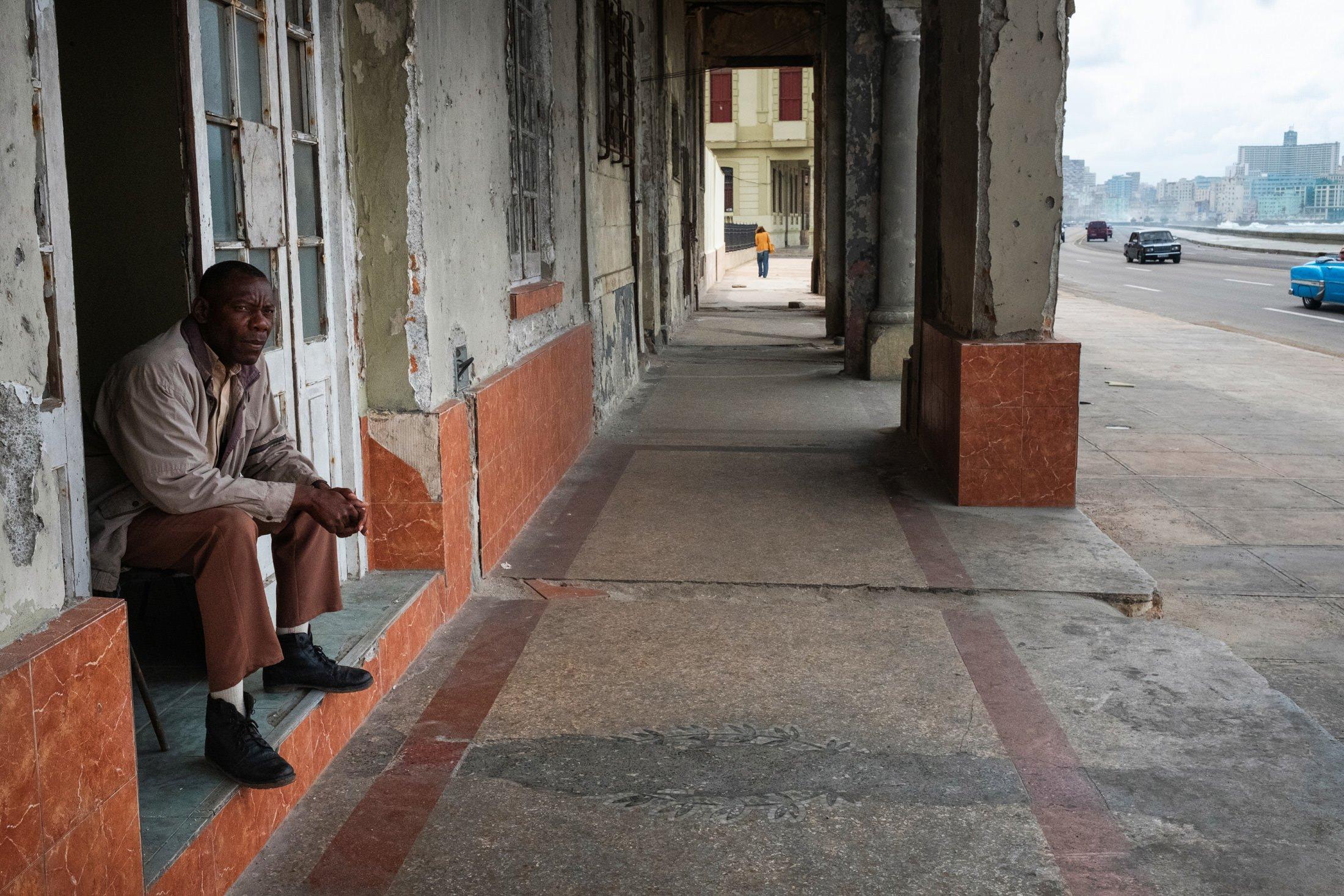 man sat on a steps in Havana, Cuba