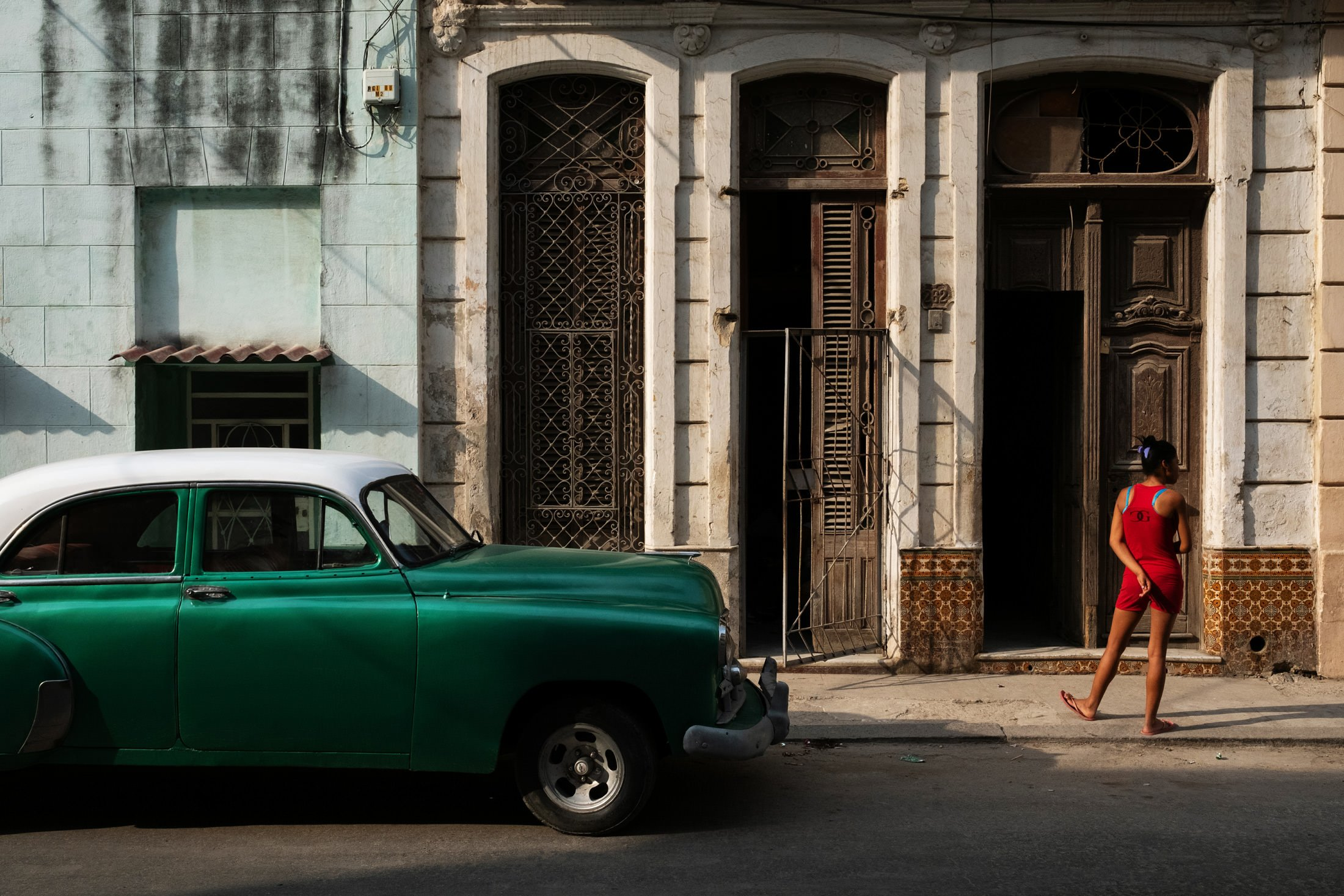 green and white cuban car with a little girl standing next to it
