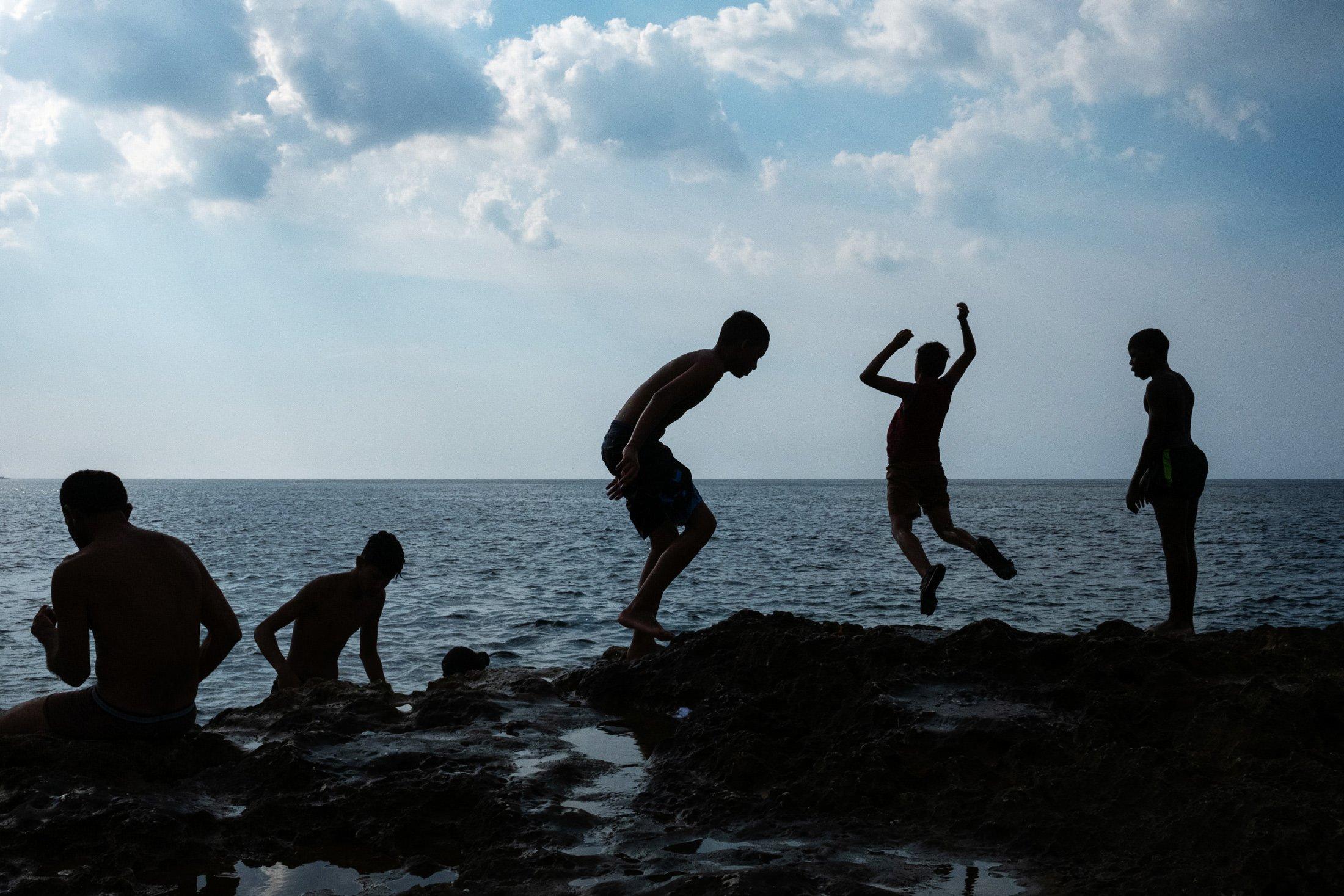 five children jumping off a wall