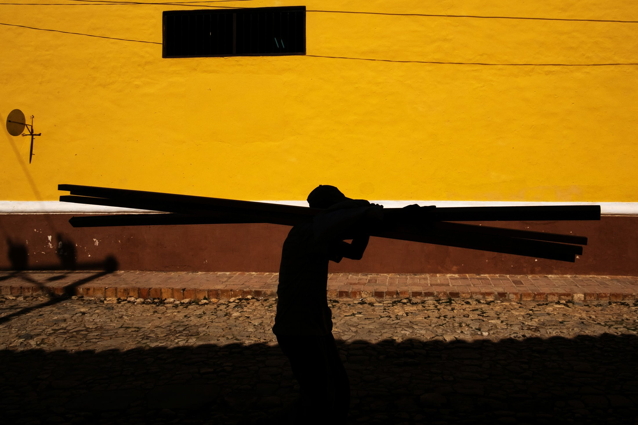silhouette of a man holding some planks