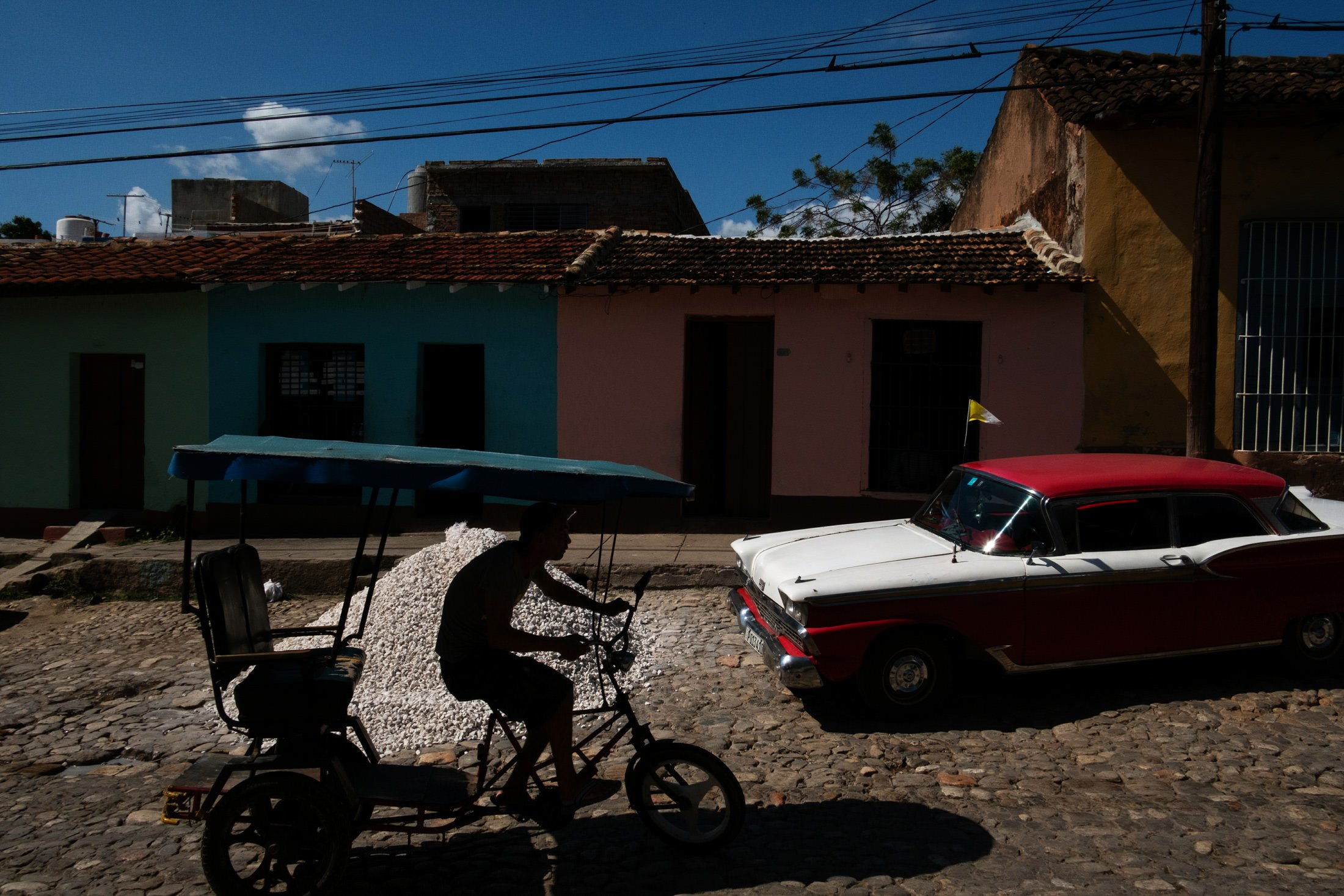 man on a bike and a red and white cuban car in Trinidad, Cuba