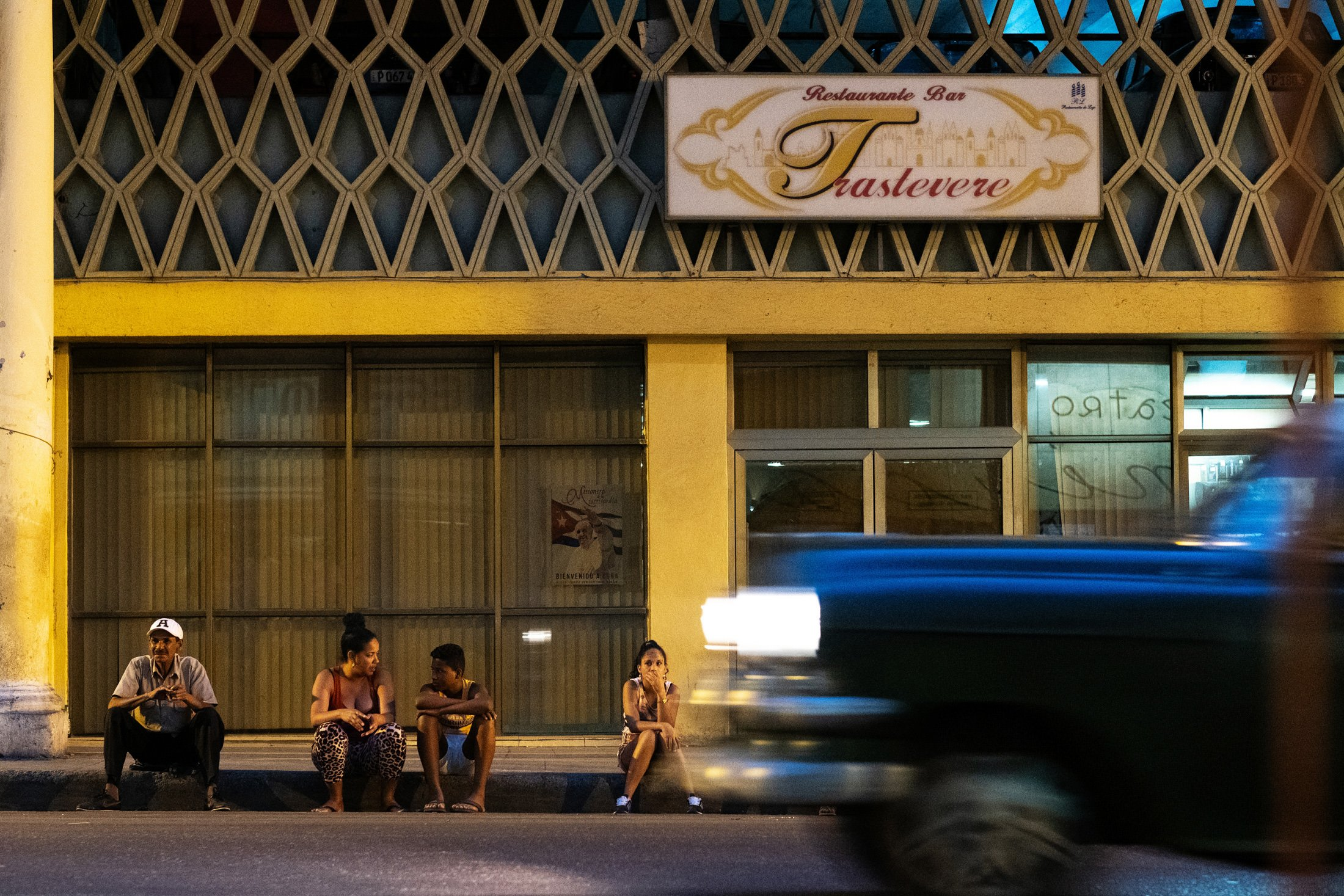 four people sat on a step at midnight on Havana's Malecon