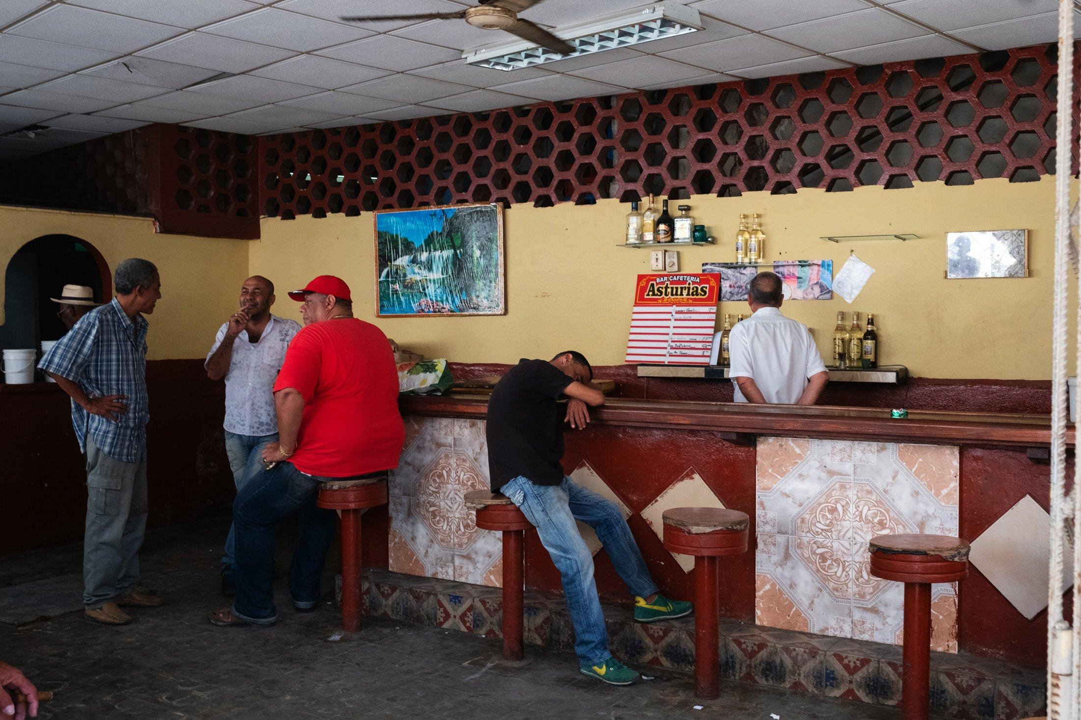 man slumped on a bar in Havana, Cuba