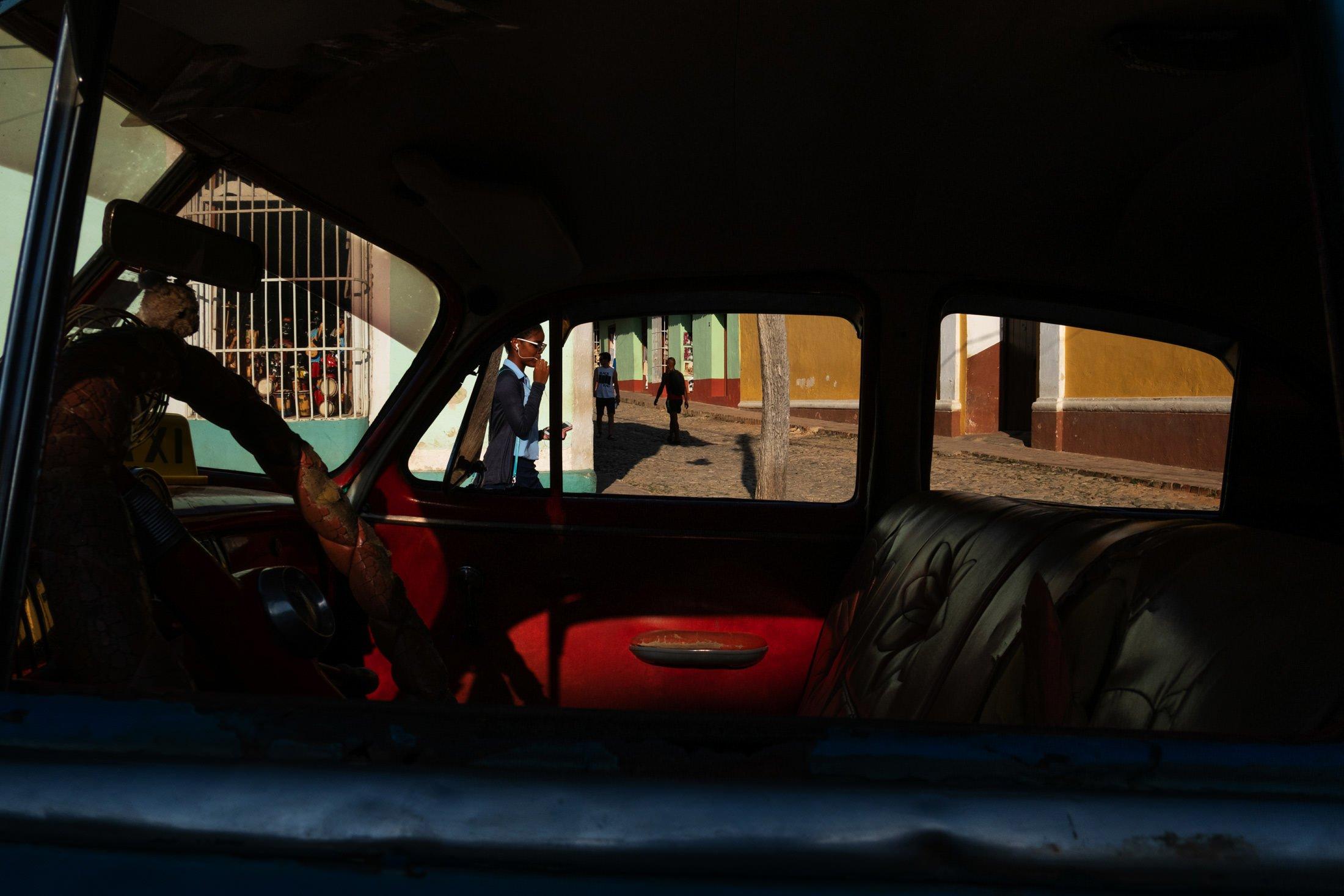 shooting through the car window, girl walking past on her ear phones in Trinidad, Cuba