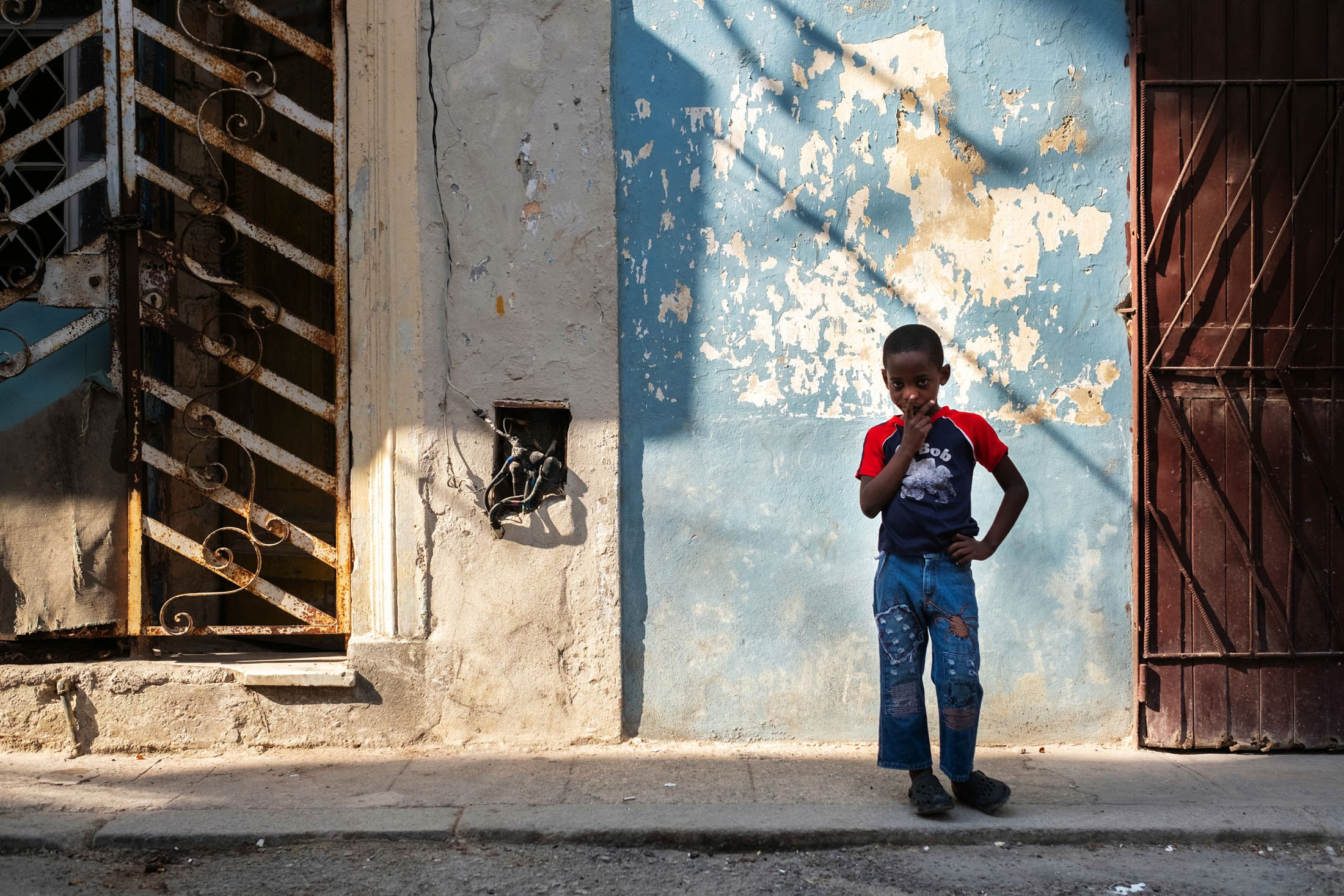 boy standing next to a blue cracked wall