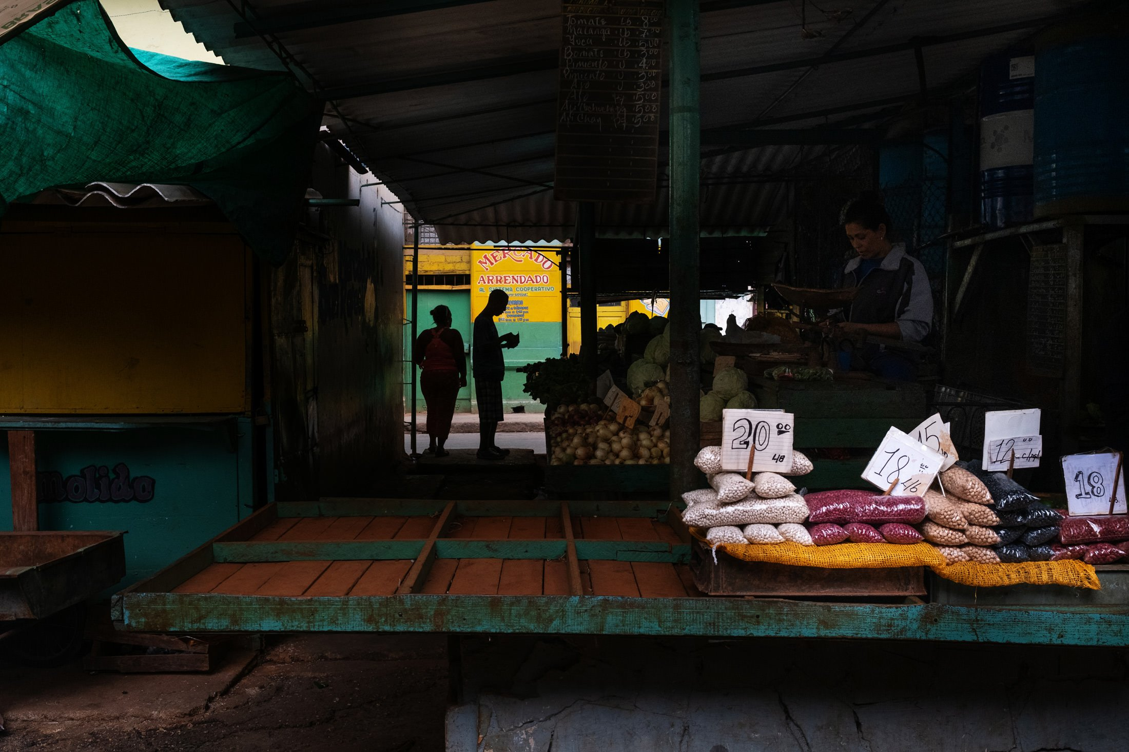 vegetable stall with two people silhouetted