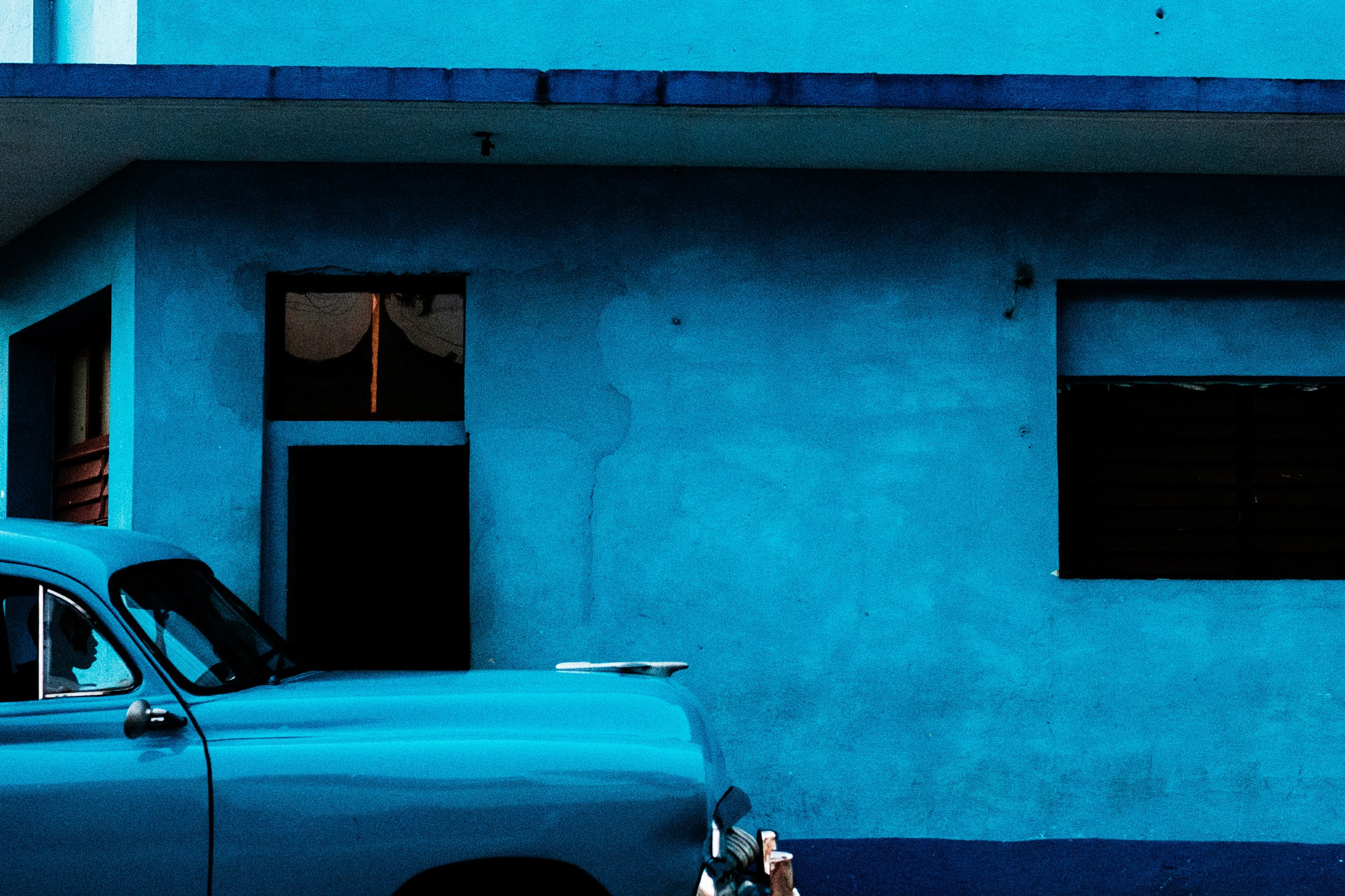 a man sat in a blue car next to a blue wall