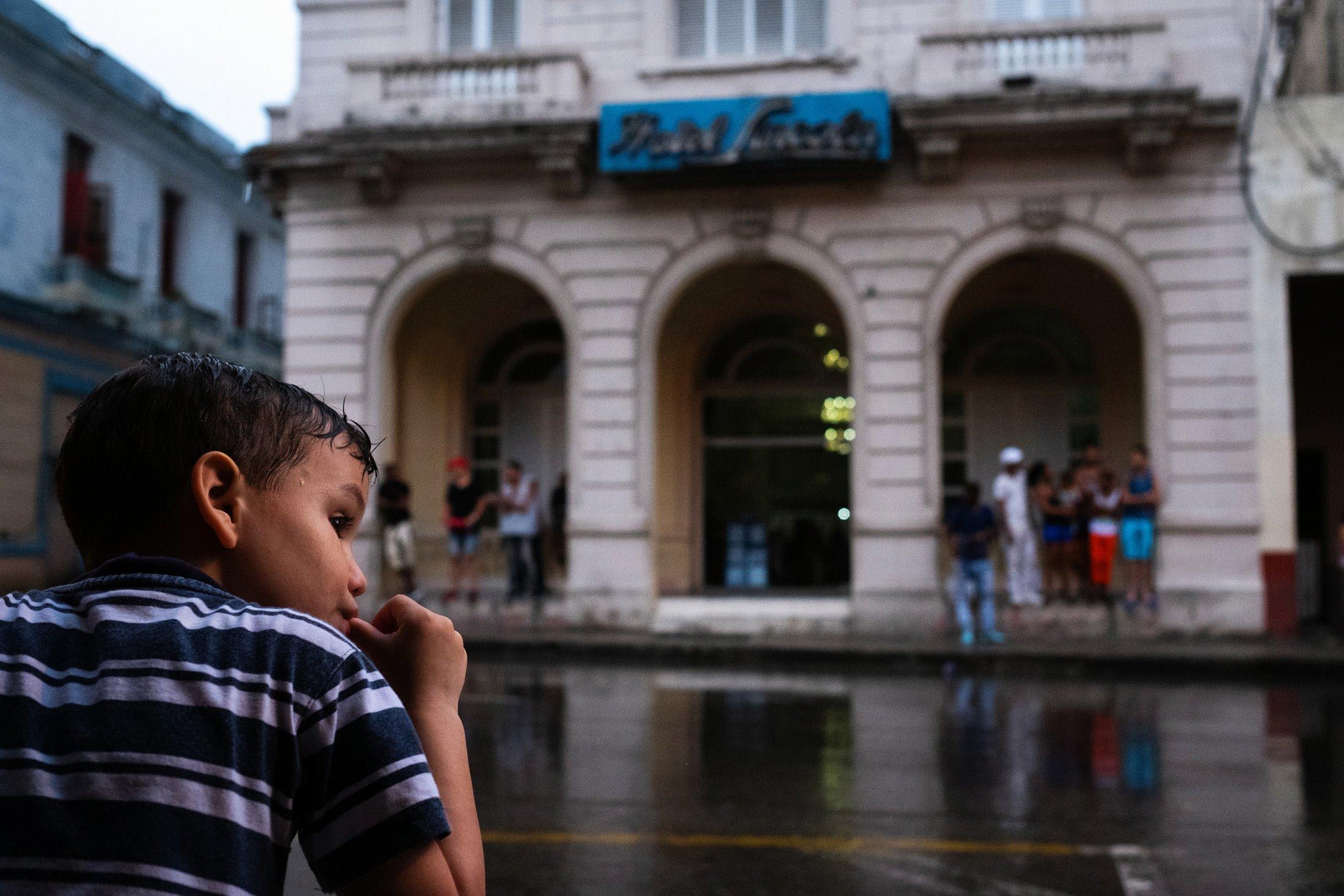 young boy sucking his thumb in the rain in Havana, Cuba