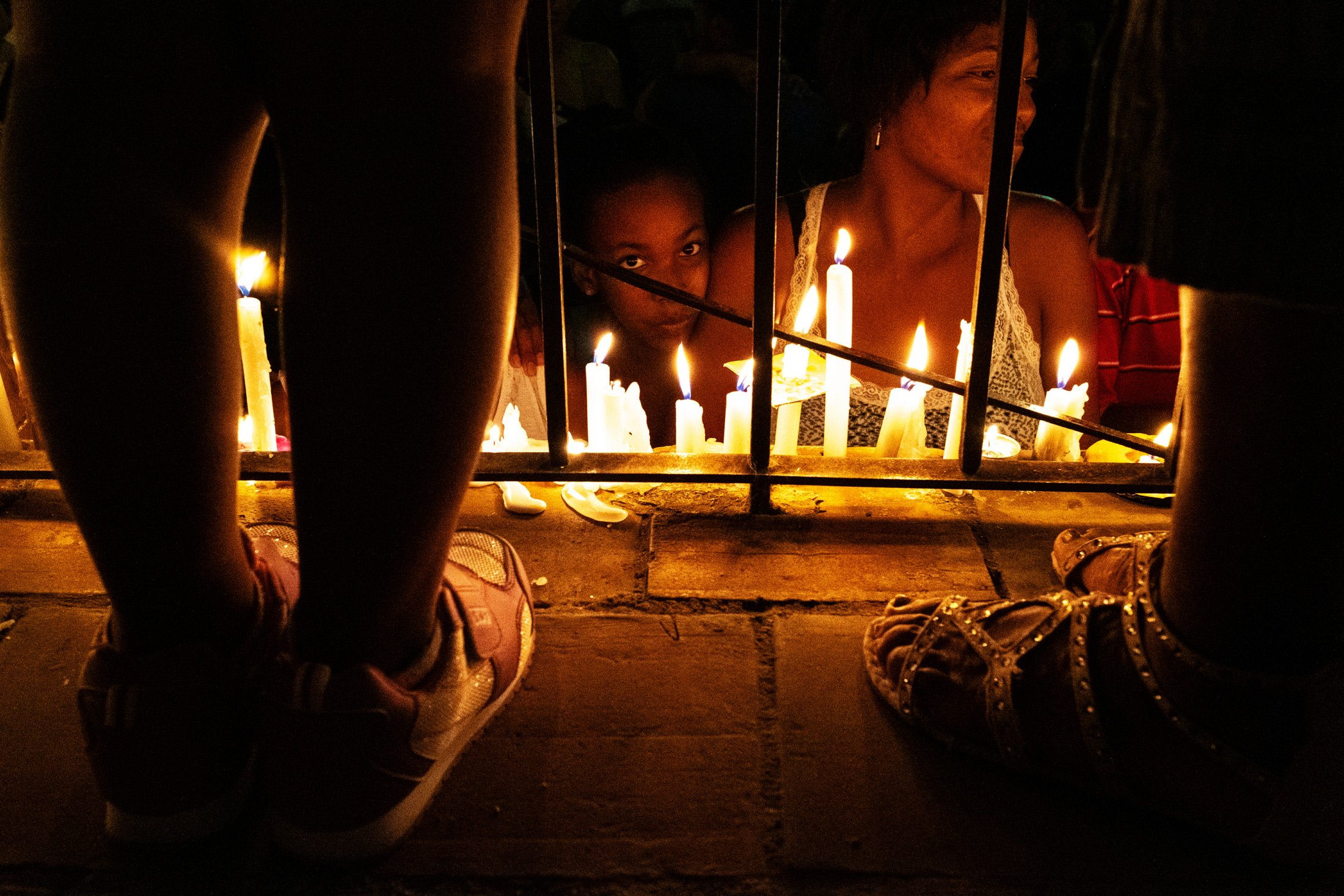 young girl surrounded by candles with two feet framing them