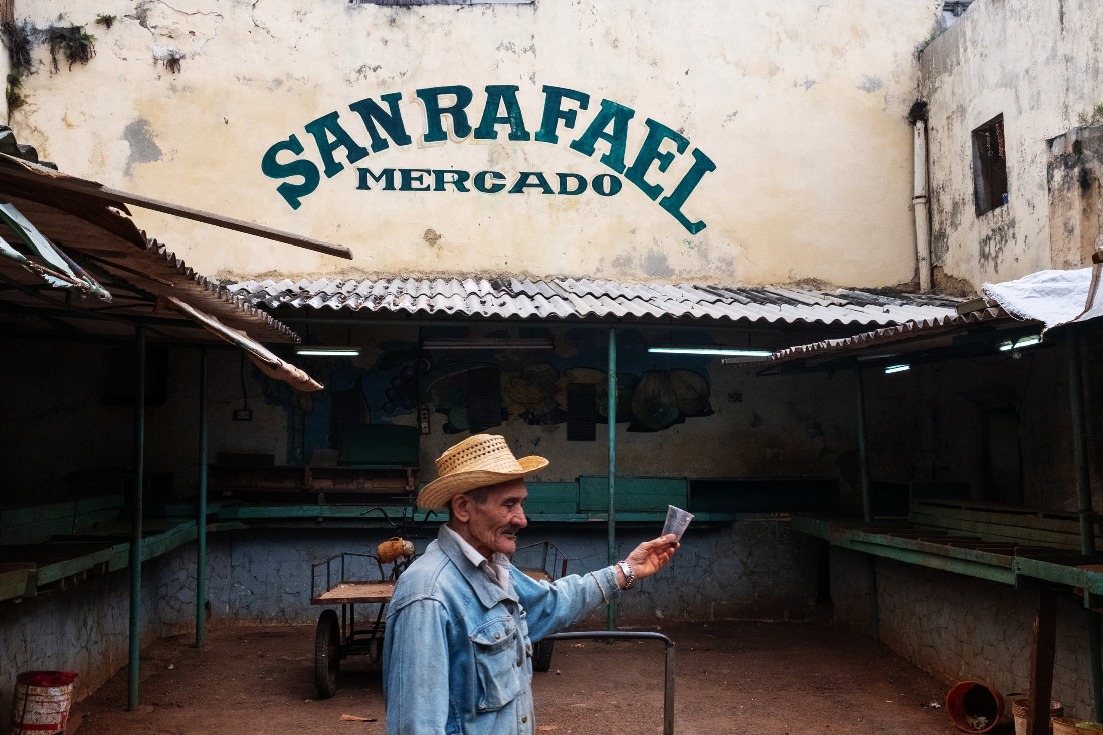 man with a glass next to a San Rafael sign
