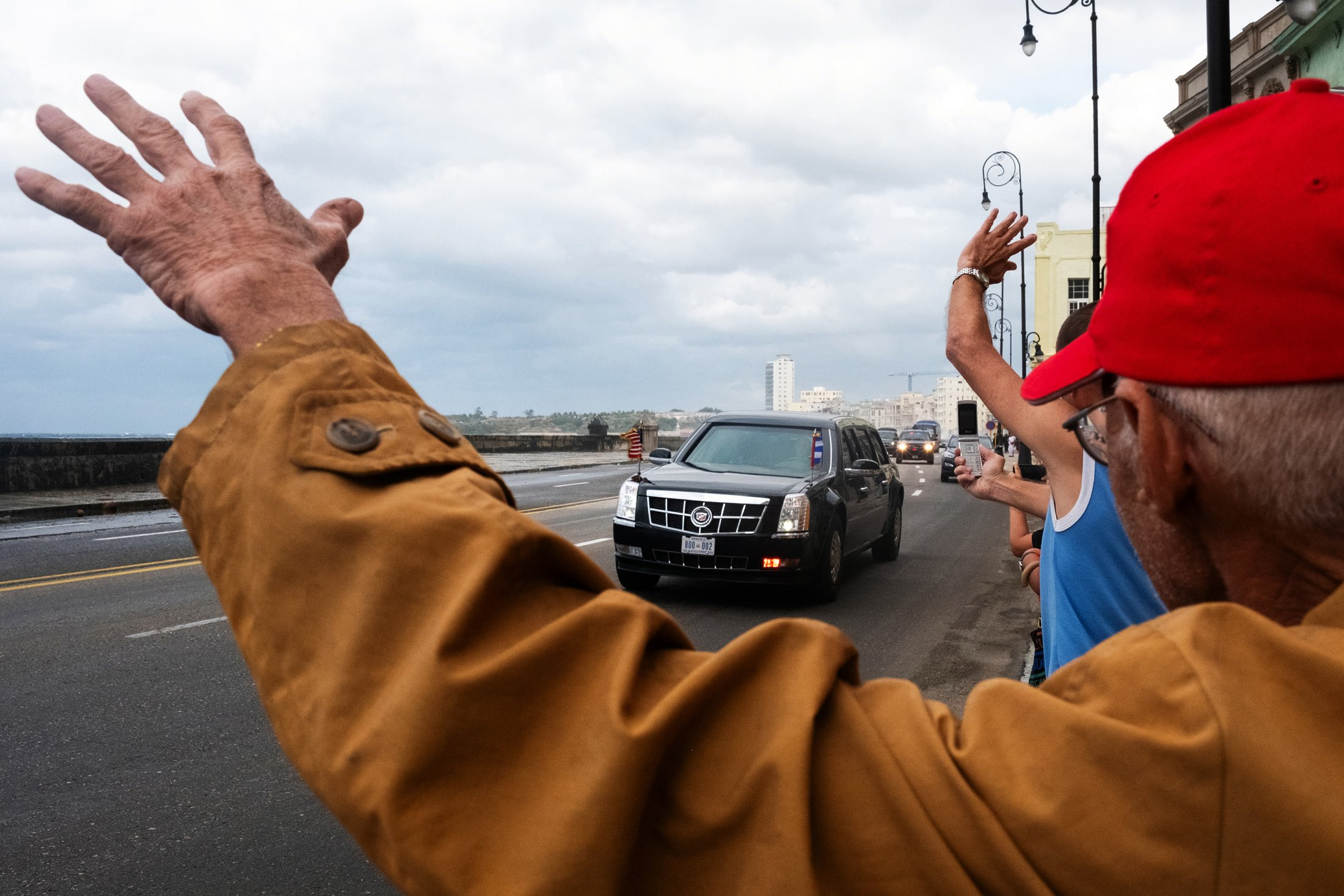 man waving at President Obama's car