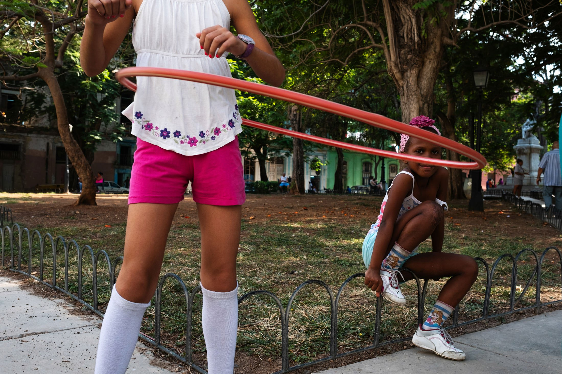 a child playing with a hulla hoop, another girls face framed in the hoop
