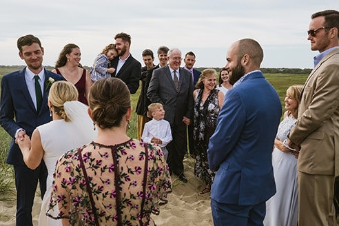 Bride and groom during outdoor beach wedding ceremony in Nantucket stand to left of frame surrounded by smiling guests. Example of a candid, documentary image during a ceremony