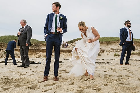 Good example of strong clean composition in a documentary wedding photograph with multiple simultaneous moments. Bride and groom stand, separated, at the centre of the image with groom looking left and bride laughing as she tries to lift her dress from the sand. To the right a guest stands in the distance looking right. On the left of the frame another guest mirrors his stance looking to the right. Next to him another guest, further back, searches for something in the sand facing away from camera. Between the bride and groom further guests gather between sand dunes.