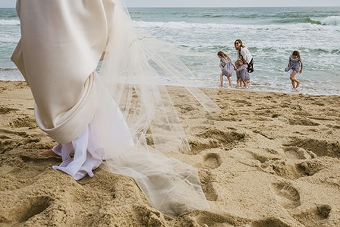 Example of unorthodox framing in a documentary wedding photograph. To the left of the frame the bottom (cropped below waist height)of the bride's dress can be seen being lifted away from the sand below. To the right and in the distance a mother and 3 children are paddling in the sea with waves crashing behind.