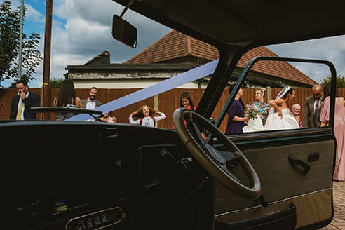 Documentary wedding photograph of wedding guests taken through a car and framed in windscreen and driver window