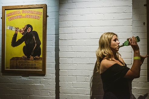 Street style wedding image at London wedding reception. Left of image is a poster of a chimpanzee drinking from a bottle. On the right of the image a woman drinks from a bottle in a mirrored pose